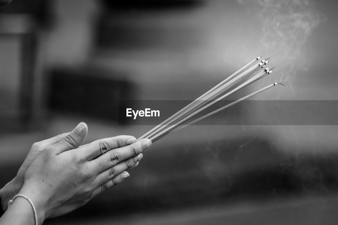 Cropped hands of woman holding burning incense sticks while praying outdoors