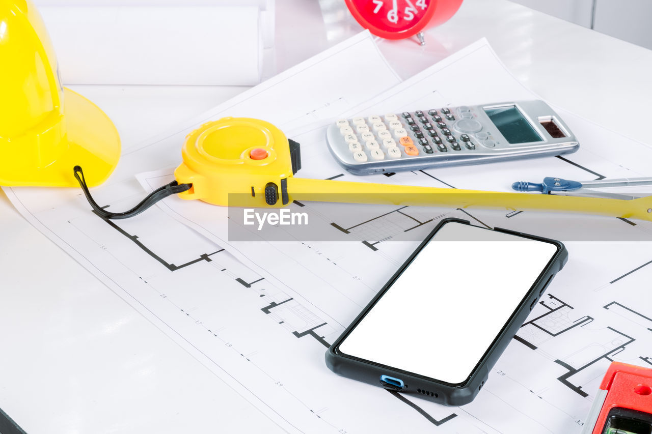 technology, connection, wireless technology, communication, pen, table, calculator, still life, indoors, portable information device, business, paper, high angle view, yellow, no people, computer, close-up, mobile phone, blueprint, office, keyboard