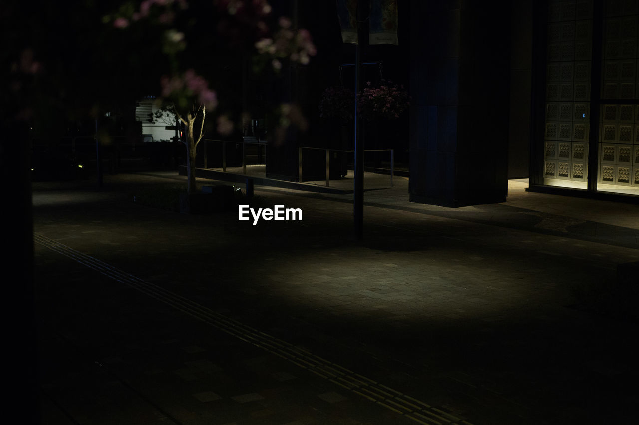 EMPTY STREET BY ILLUMINATED BUILDINGS AT NIGHT