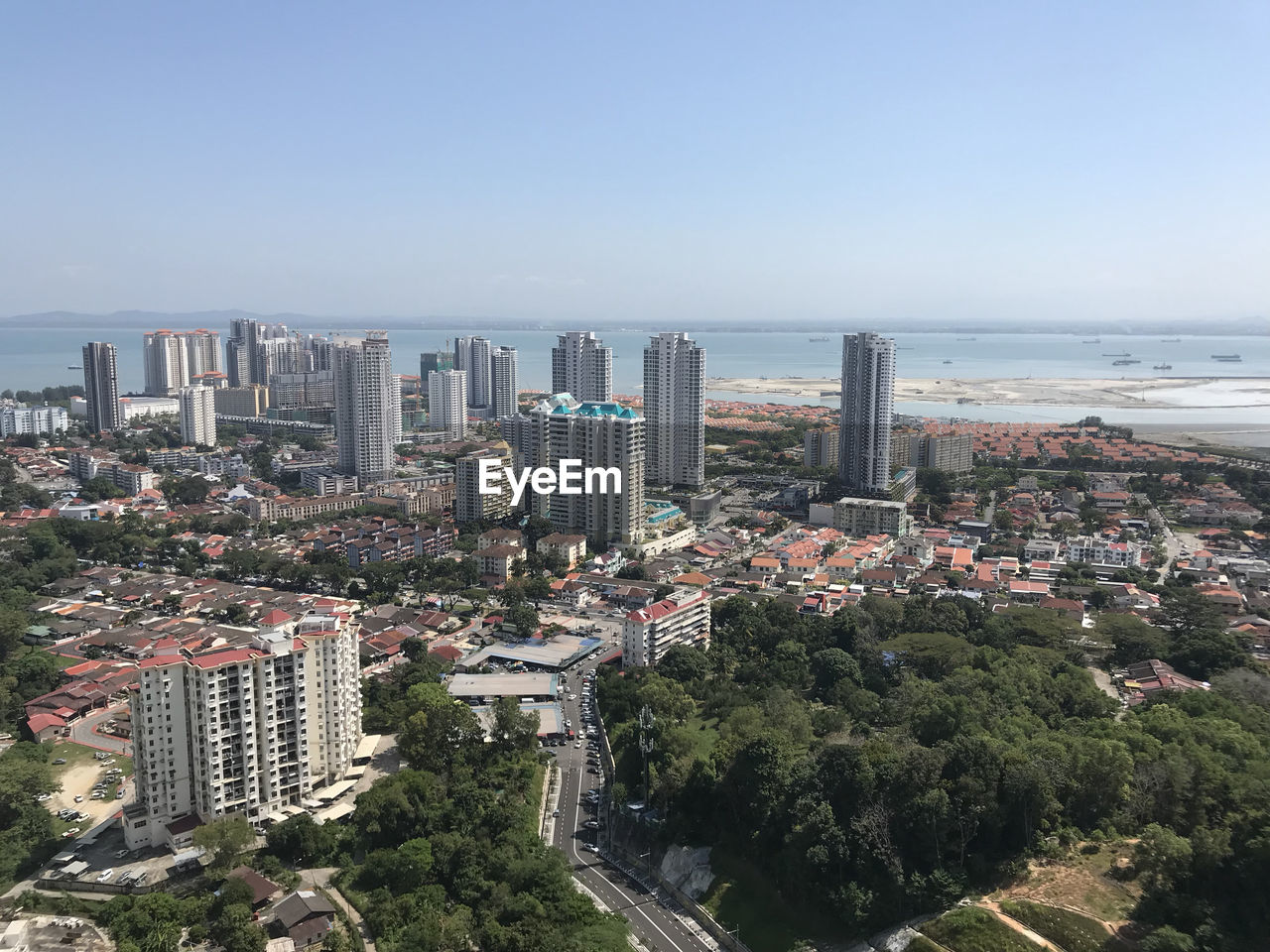 architecture, cityscape, skyscraper, building exterior, city, high angle view, sea, clear sky, day, no people, built structure, tree, outdoors, downtown district, sky, modern, growth, water, urban skyline, nature