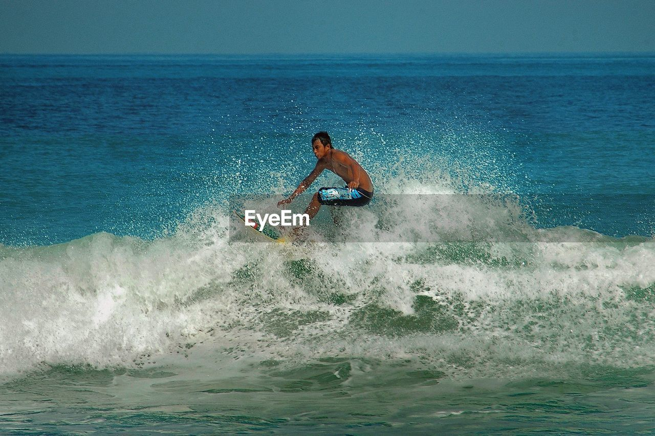 sea, surfing, one person, extreme sports, surfboard, horizon over water, balance, leisure activity, motion, real people, sport, wave, nature, water, adventure, men, skill, waterfront, day, lifestyles, outdoors, sky, beauty in nature, full length, one man only, jet boat, people, adult, adults only
