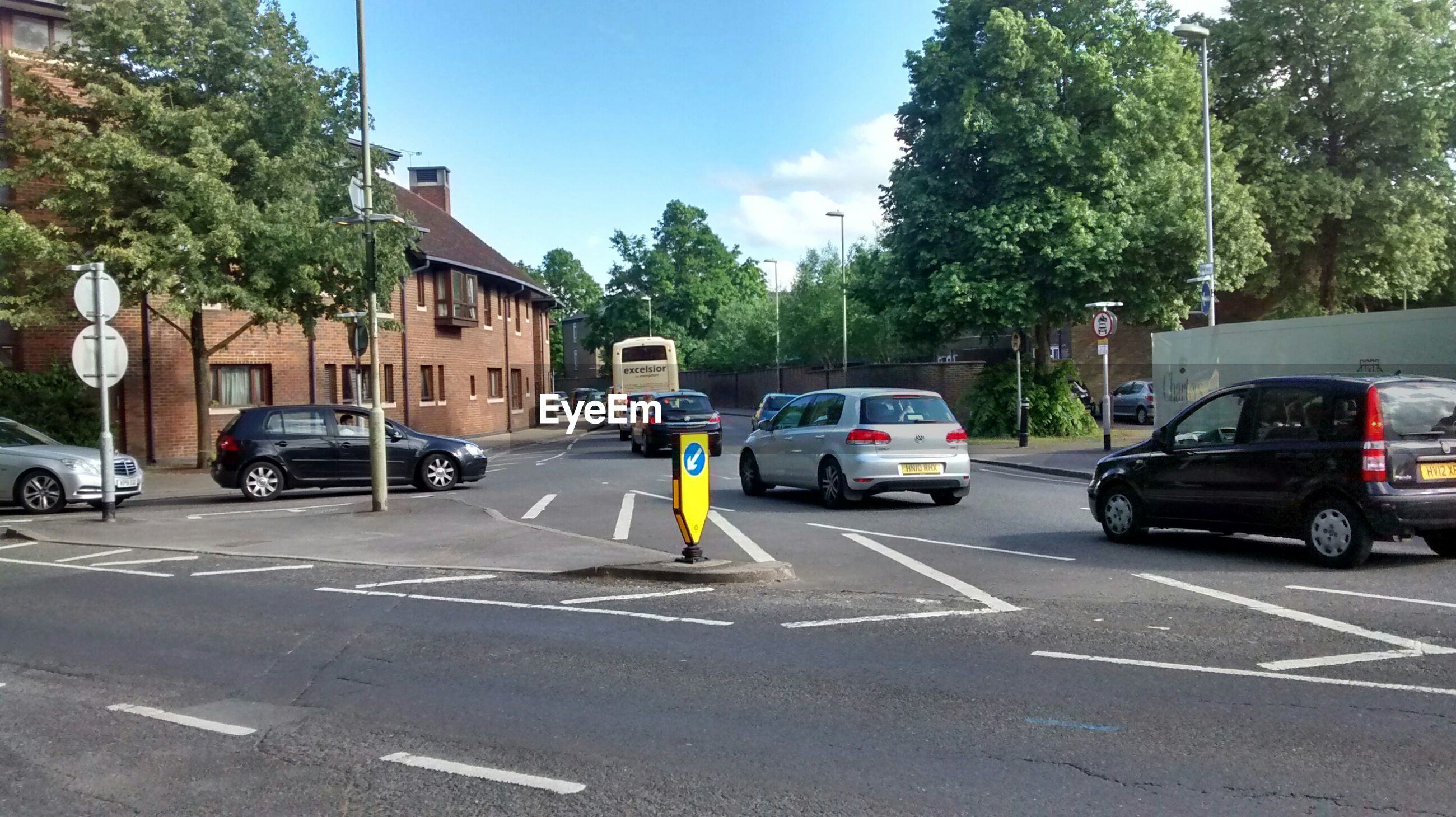transportation, car, land vehicle, mode of transport, road, street, road marking, tree, building exterior, architecture, built structure, city, the way forward, on the move, traffic, sky, city street, day, travel, incidental people