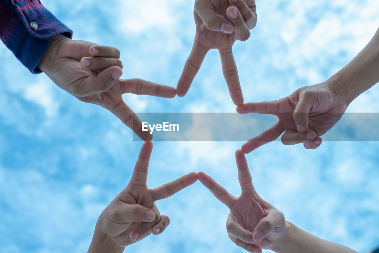 Directly below shot of people making star shape with fingers against sky