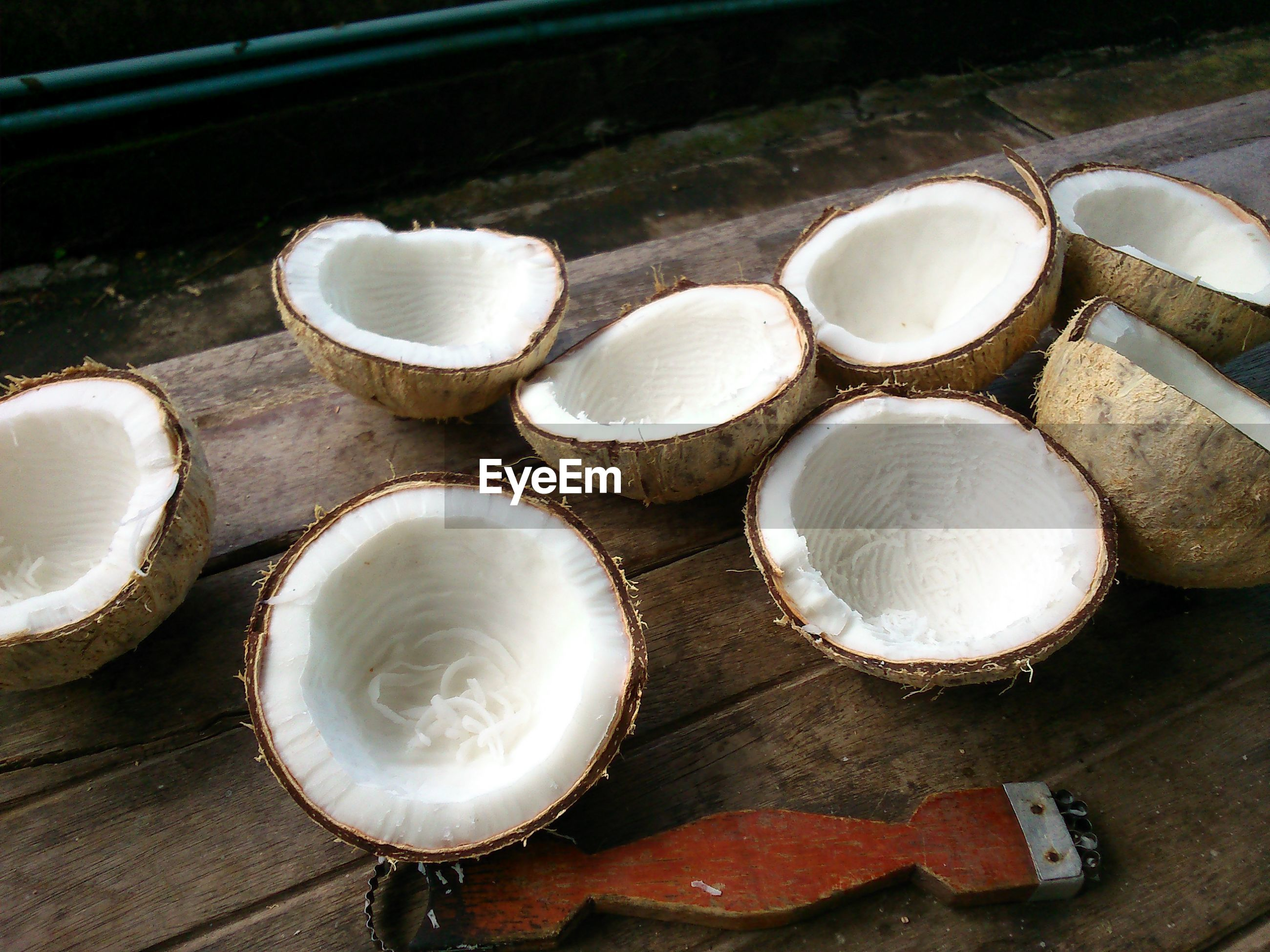 High angle view of halved grated coconuts and grater on wood