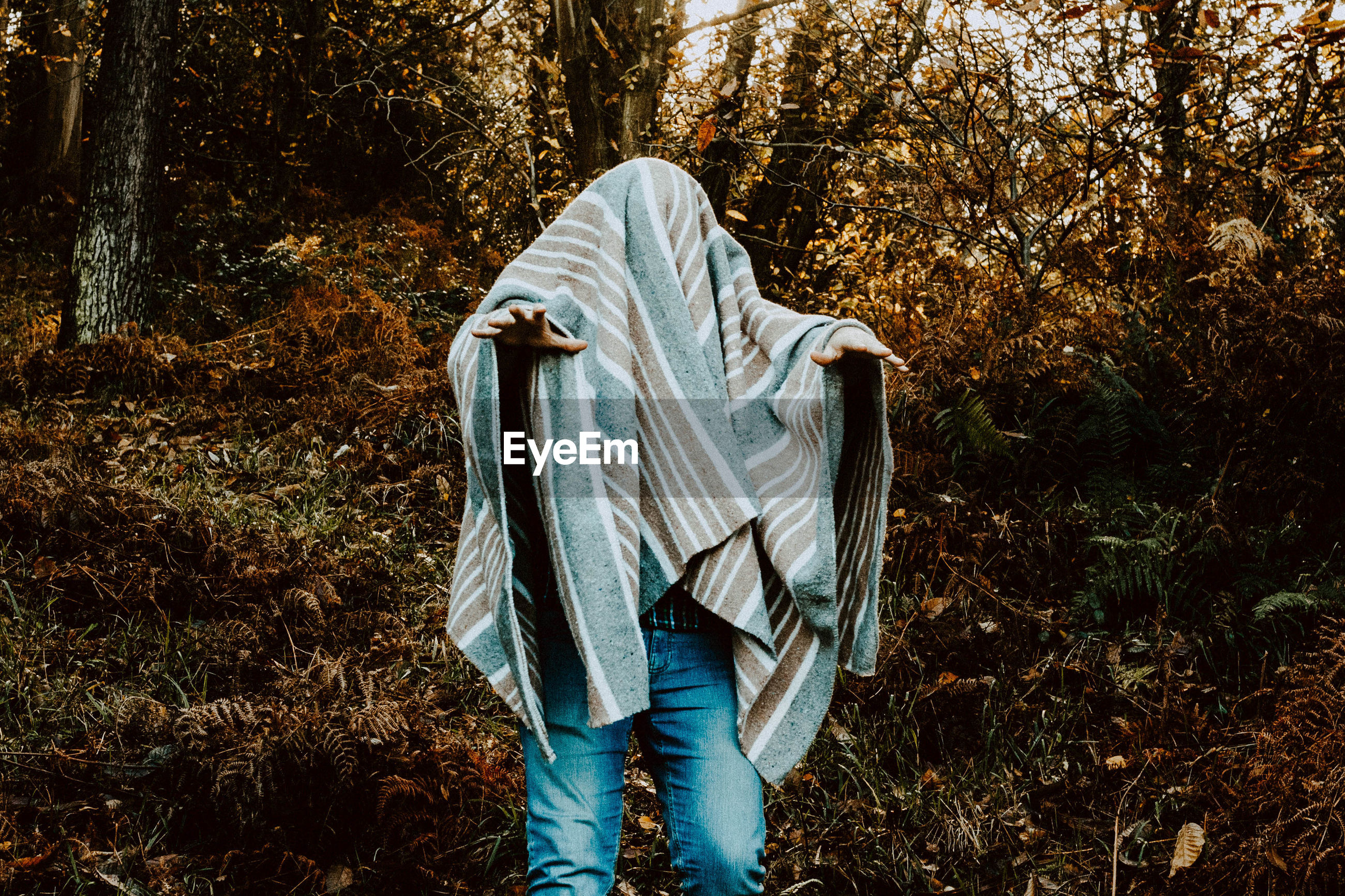 Man covered in blanket gesturing while standing in forest