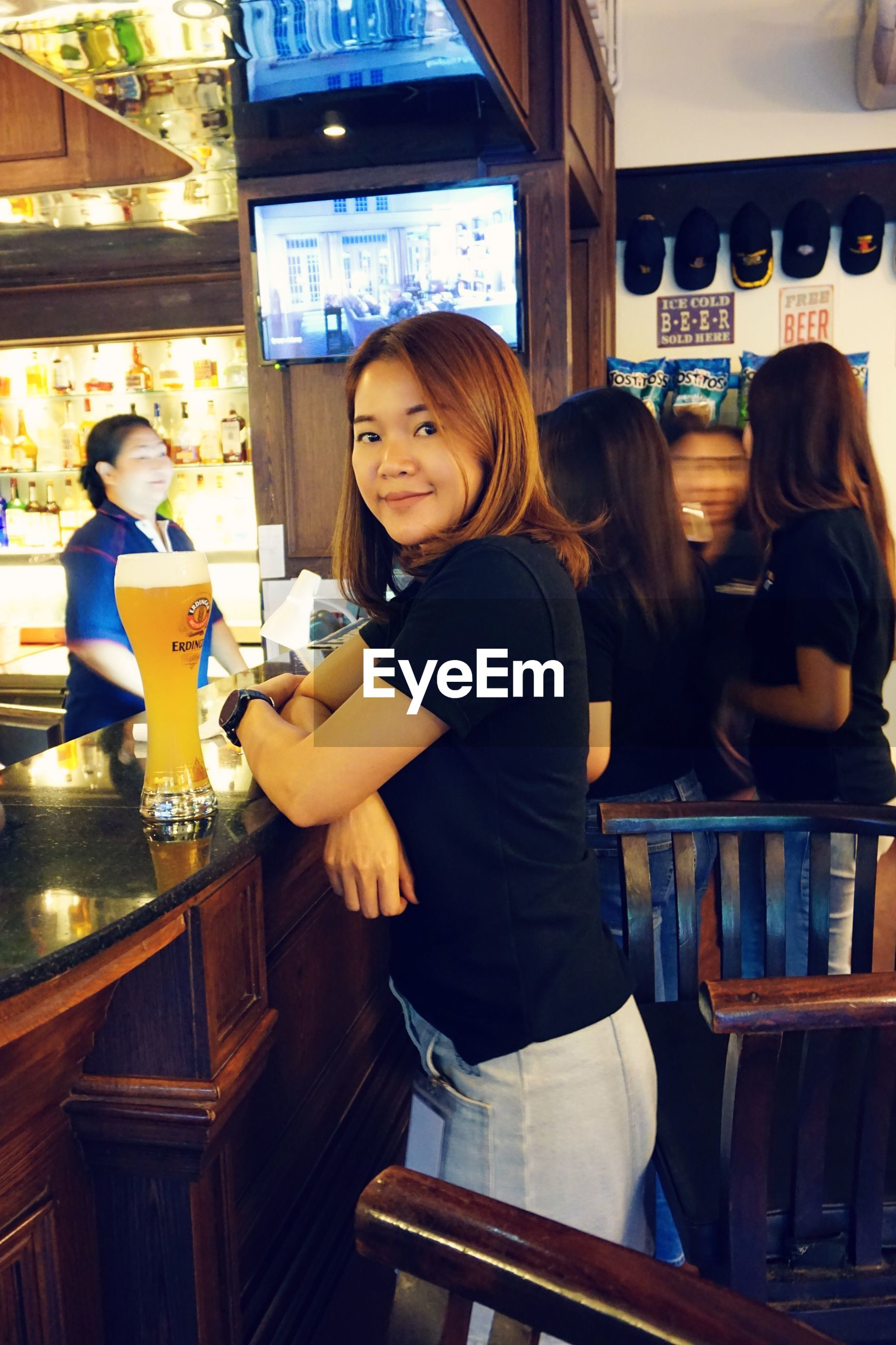 restaurant, bar counter, real people, food and drink, bar - drink establishment, smiling, standing, casual clothing, bartender, customer, indoors, cafe, young women, occupation, waitress, leisure activity, lifestyles, drink, happiness, young adult, service, two people, happy hour, day, freshness, people