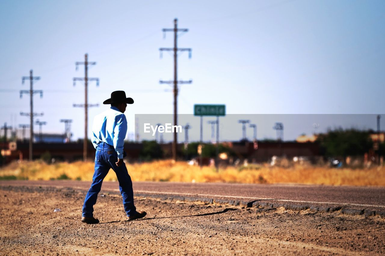 Full Length Of Man Walking On Field By Road Against Clear Sky