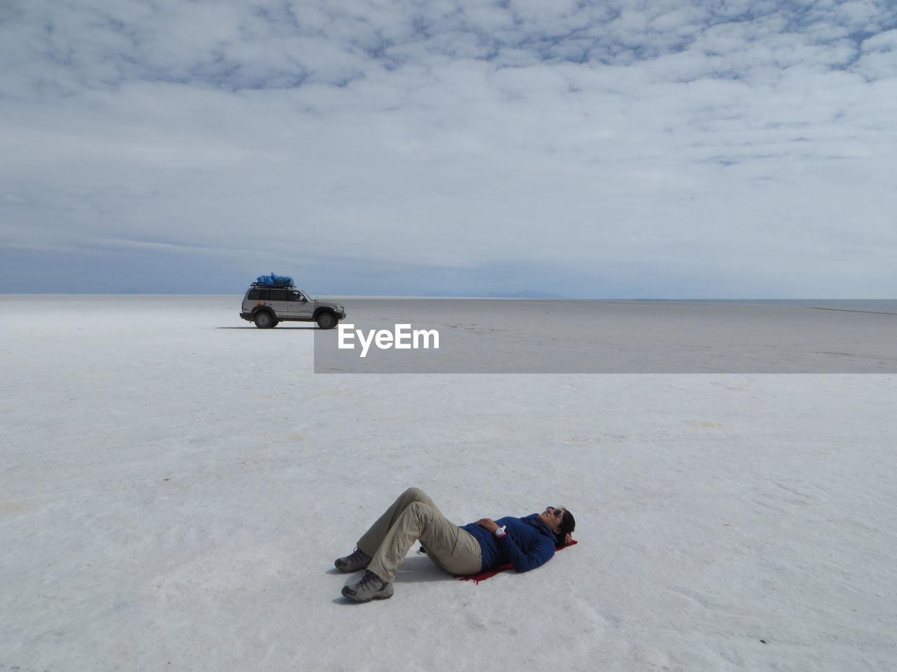 Full Length Of Woman Relaxing On Salt Flat At Salar De Uyuni