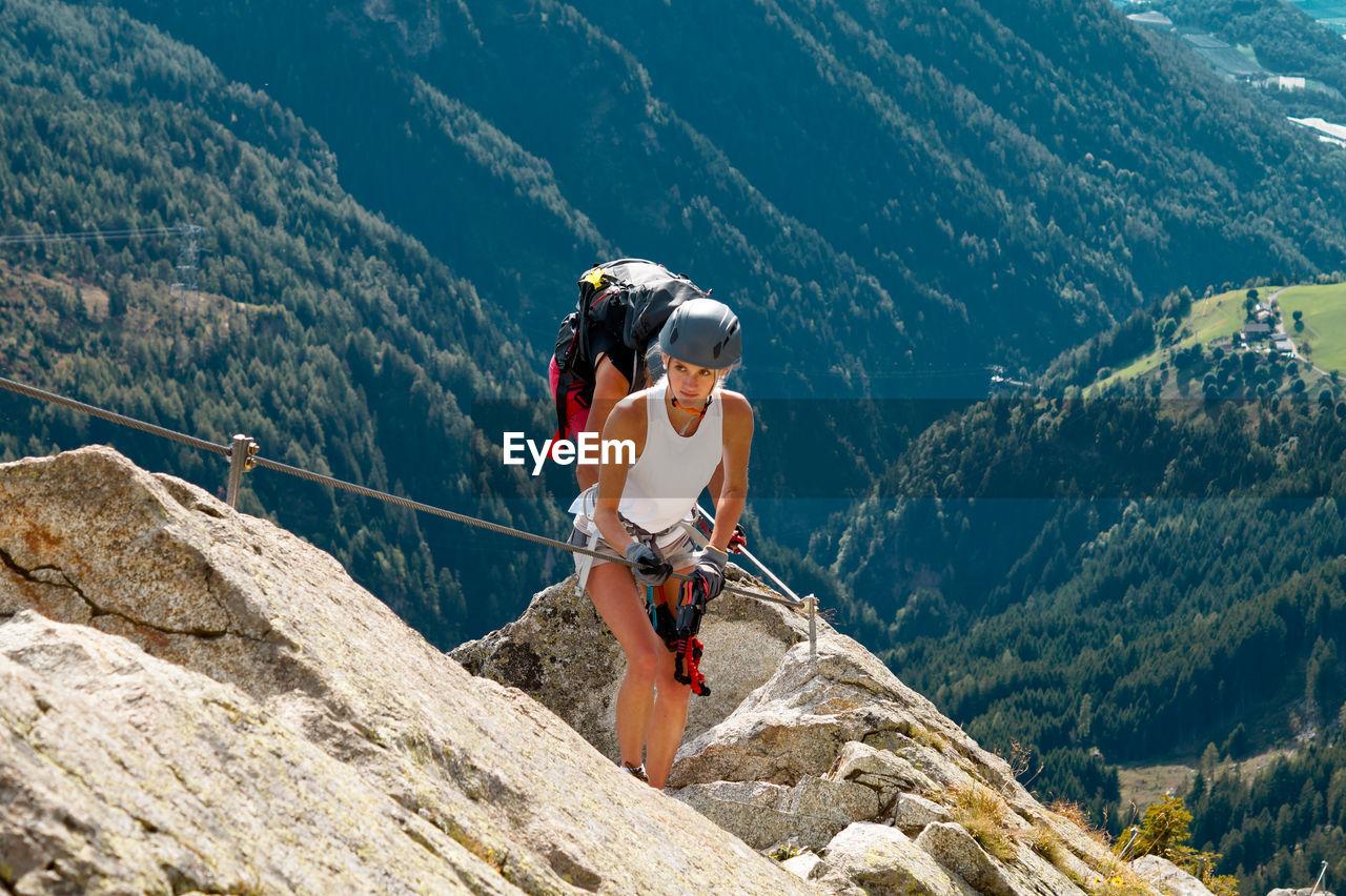 Full length of woman climbing rocks in a mountain at heini-holzer-klettersteig, meran 2000
