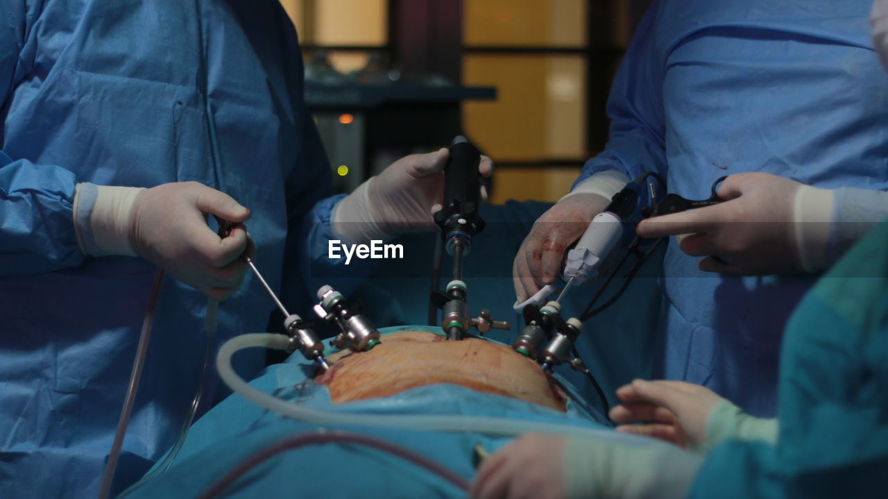 Midsection of doctors operating patient during surgery