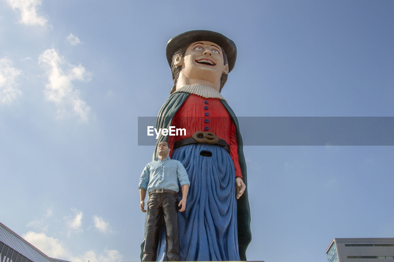 Low angle view of statues against blue sky
