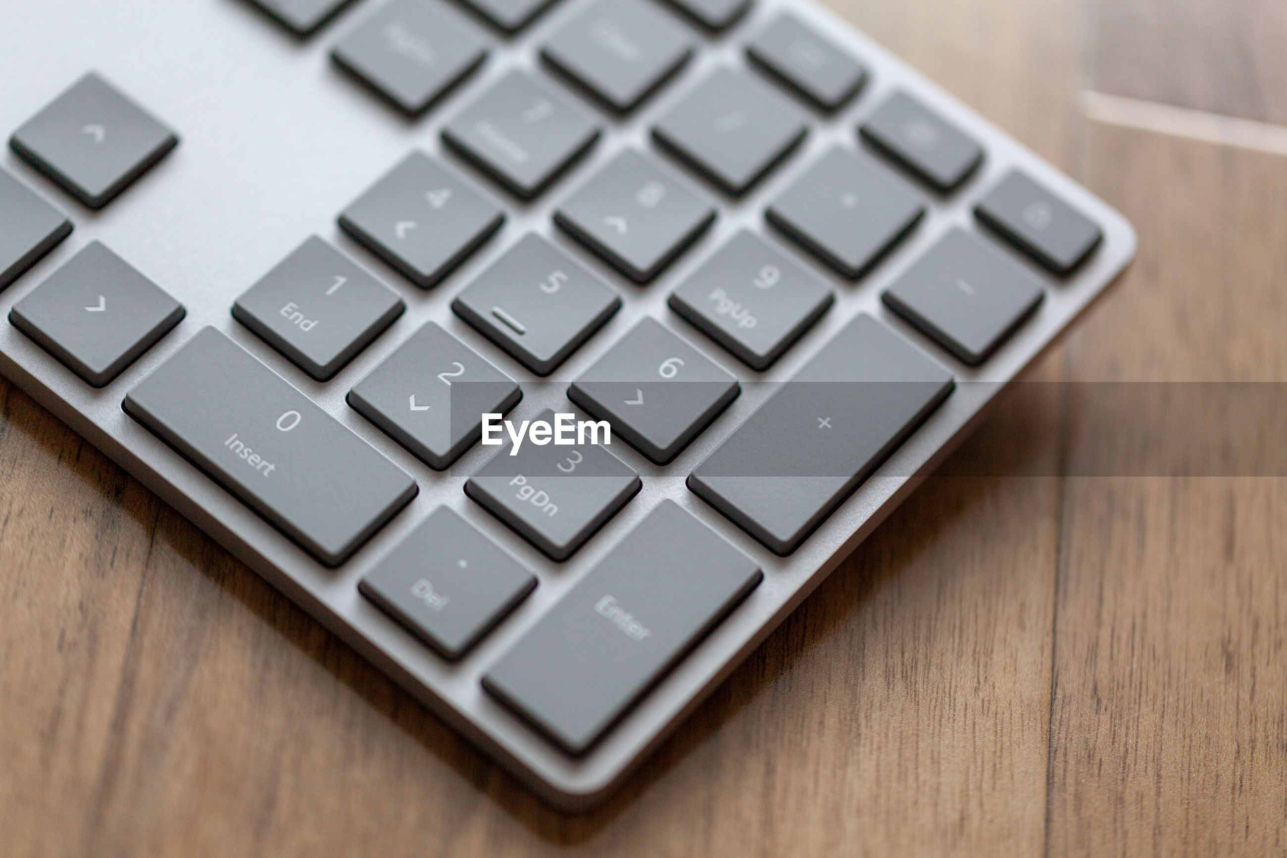High angle view of computer keyboard on wooden table