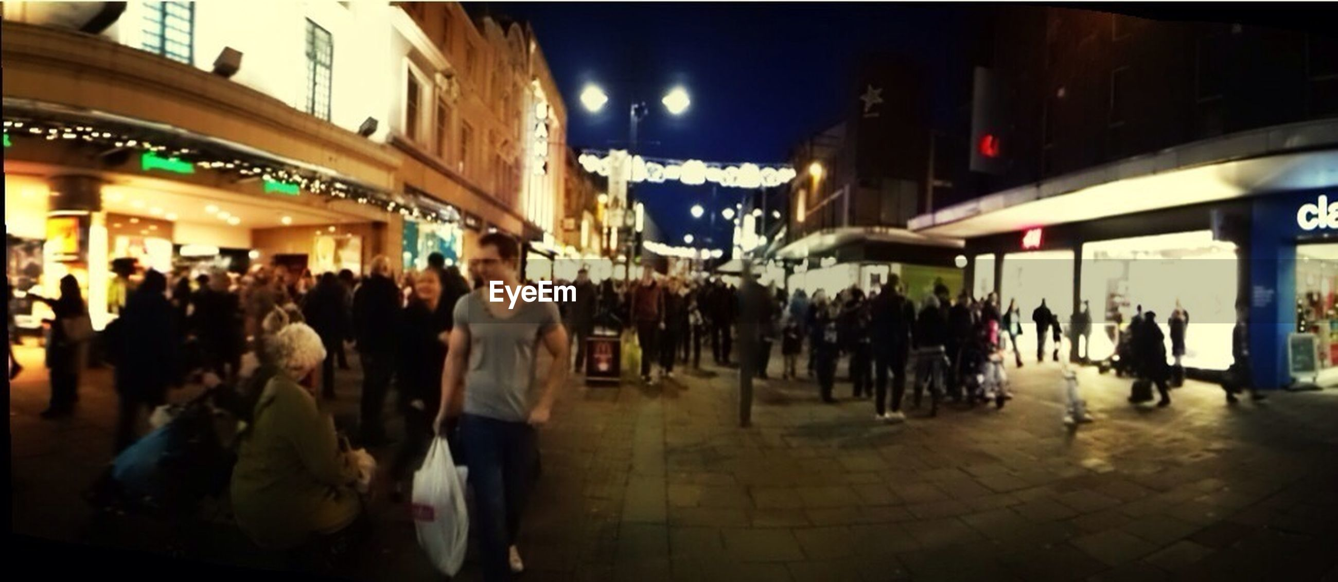large group of people, illuminated, person, night, men, architecture, city life, built structure, crowd, city, lifestyles, building exterior, lighting equipment, market, walking, leisure activity, indoors, mixed age range, street