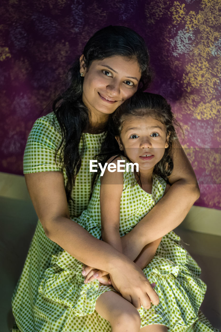 Portrait of a smiling young woman with her daughter