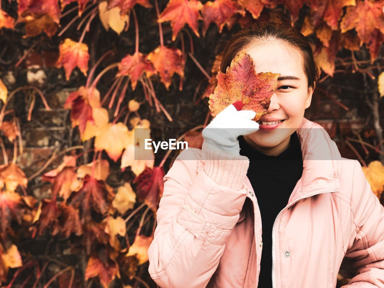 Portrait of young woman holding maple leaf during autumn