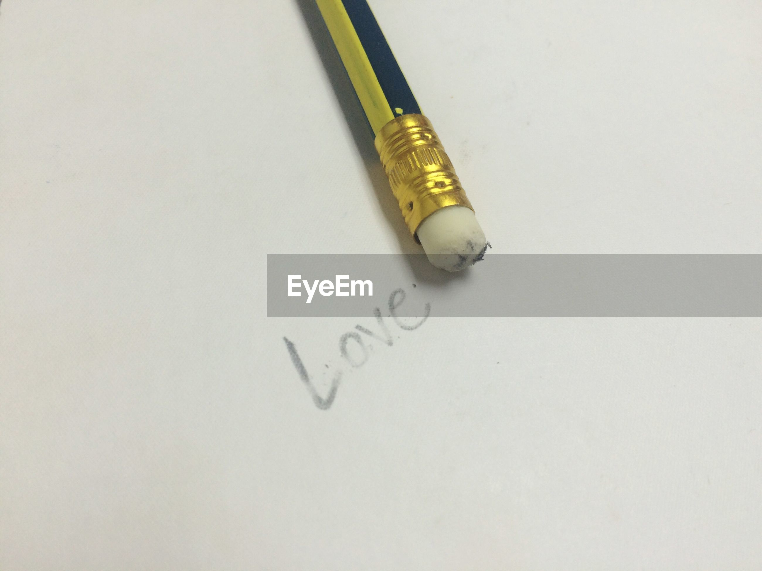 High angle view of pencil by love text erased on white background