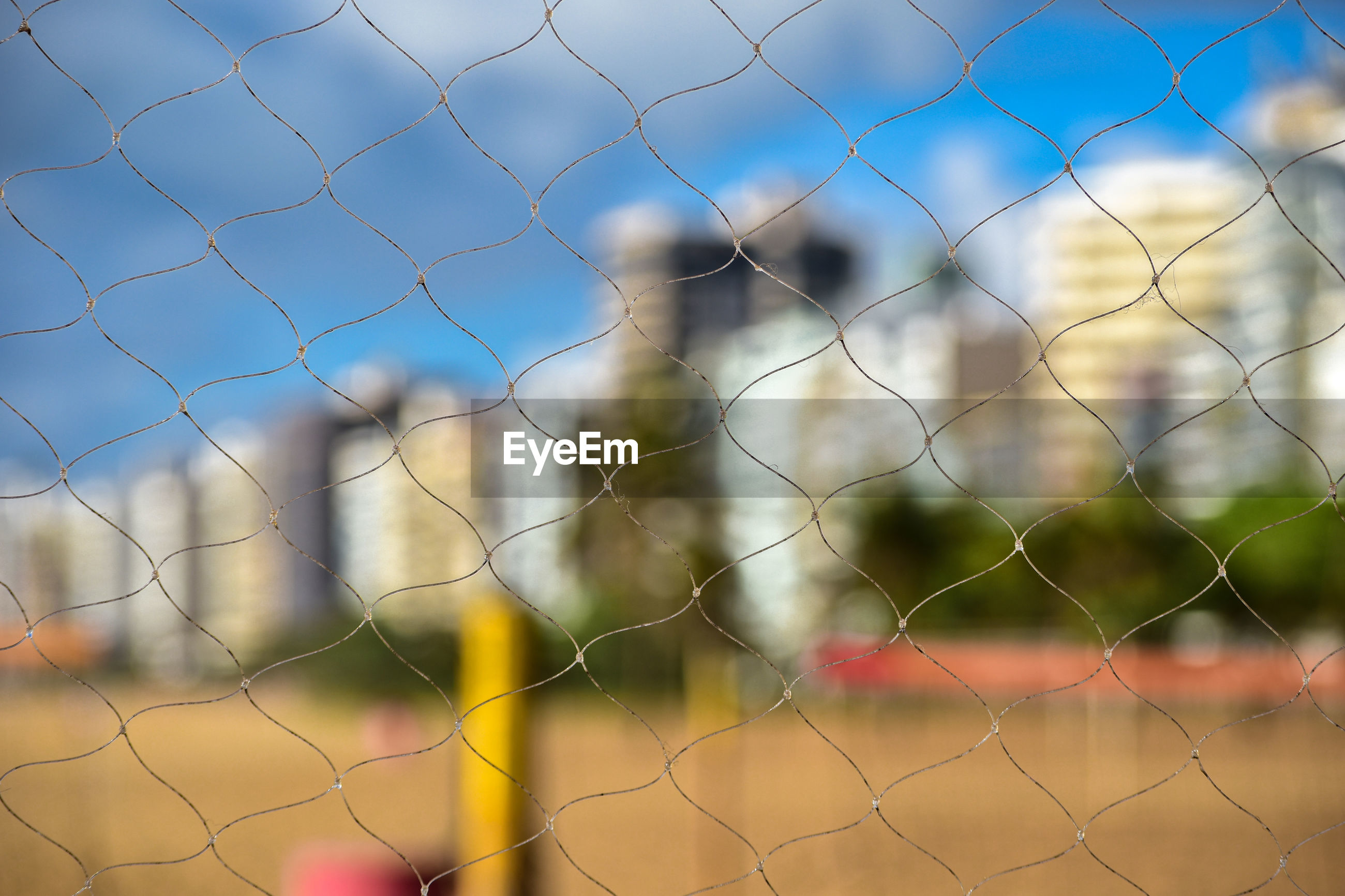 Full frame shot of fence against the sky and cityscape.