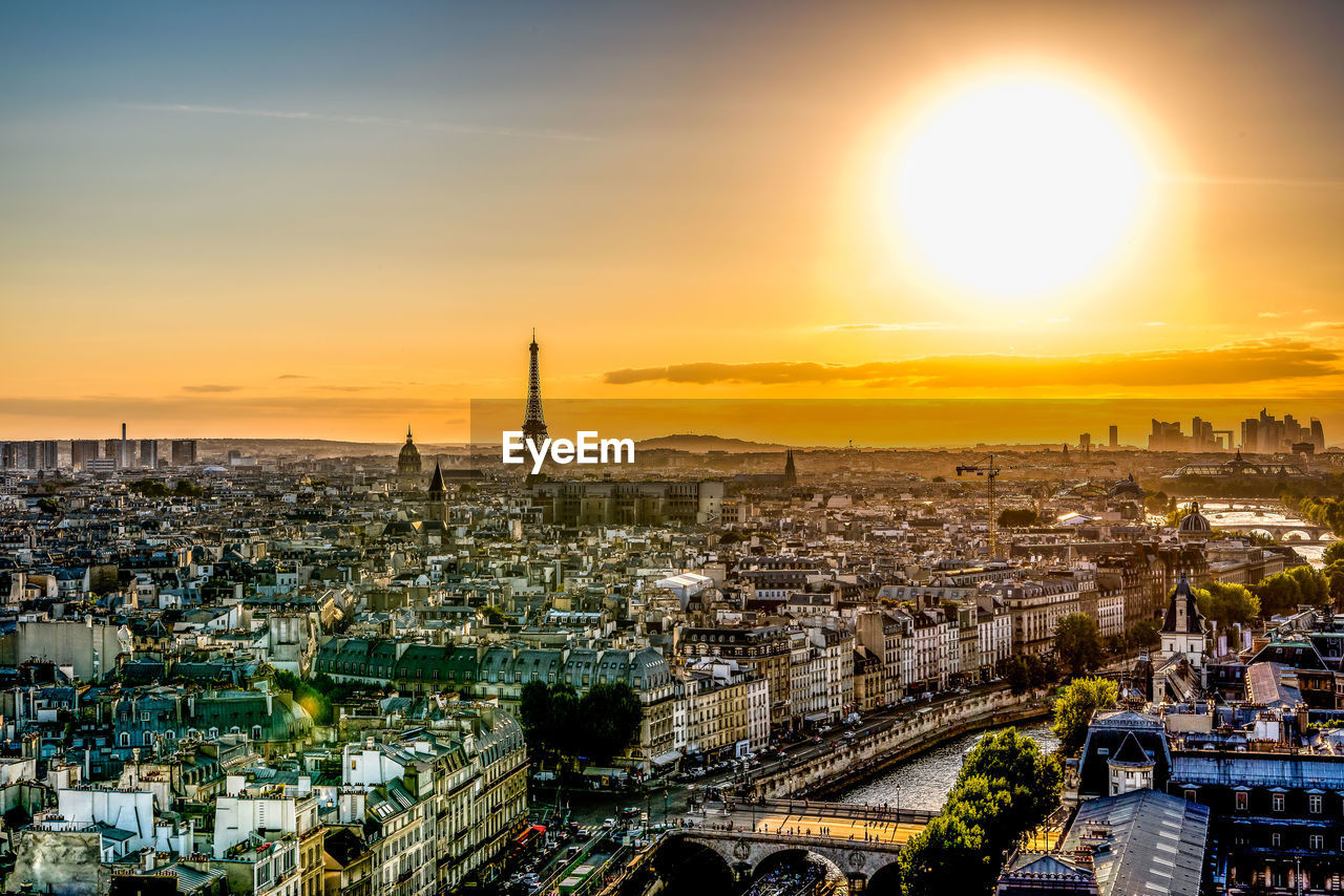 Distant view of eiffel tower amidst cityscape during sunset