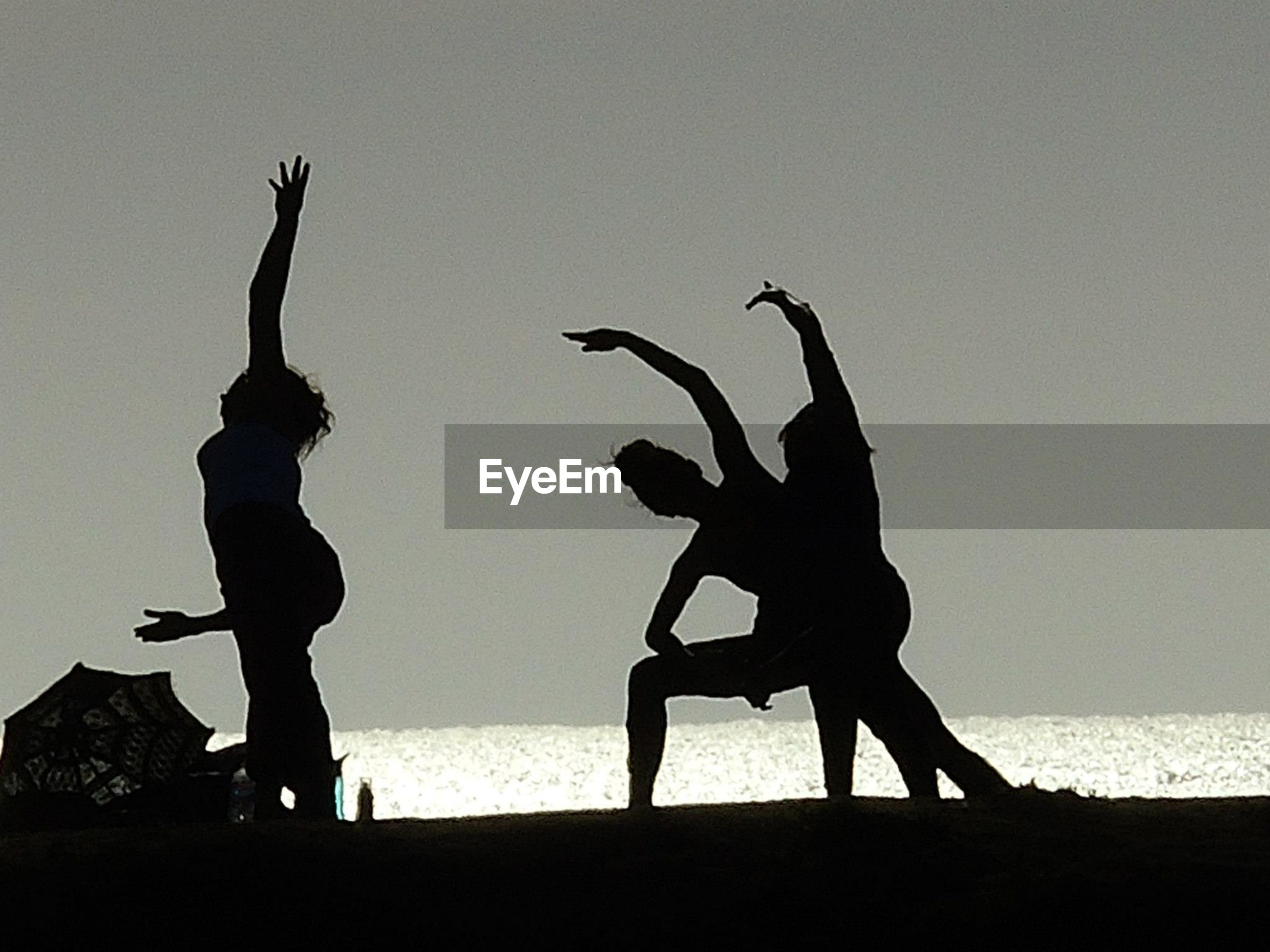 Silhouette women exercising on beach against clear sky