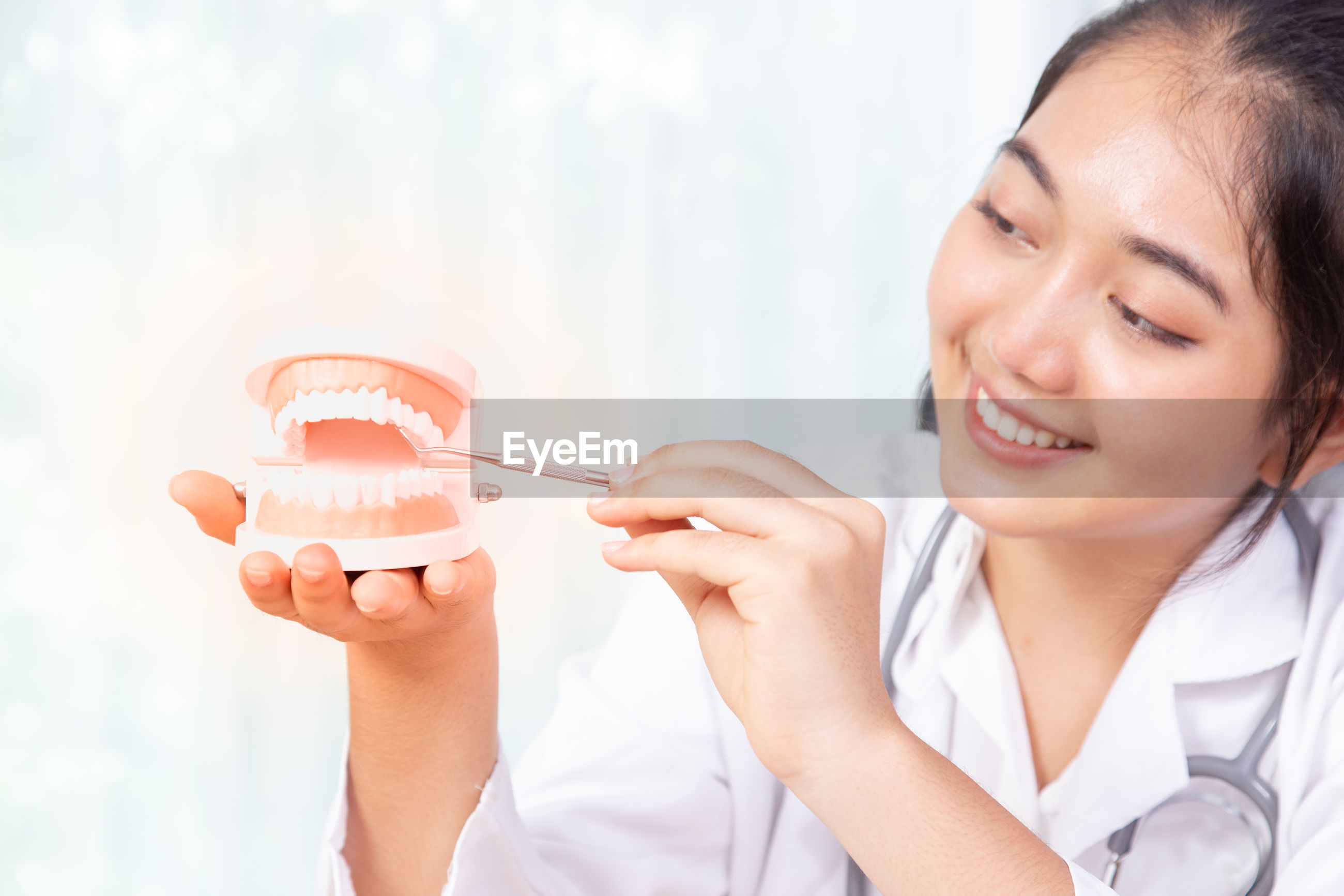Close-up of smiling doctor holding dental implant in clinic