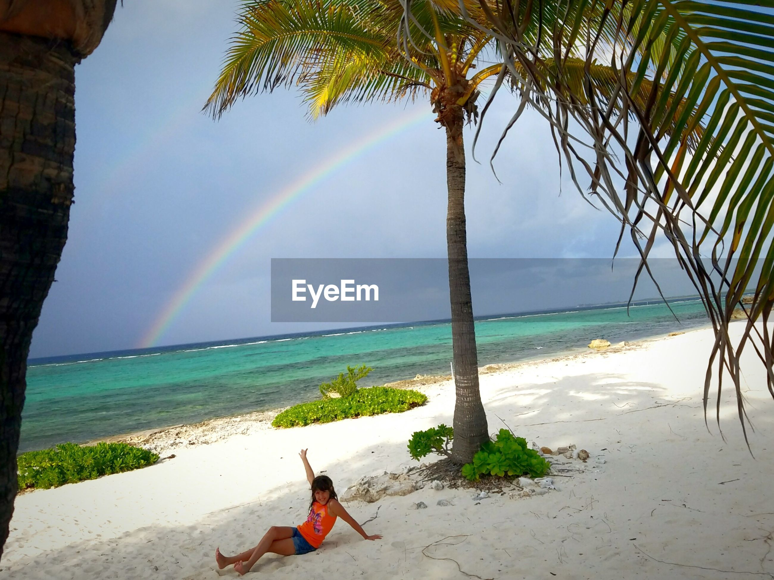 Full length of girl resting at beach against rainbow in cloudy sky