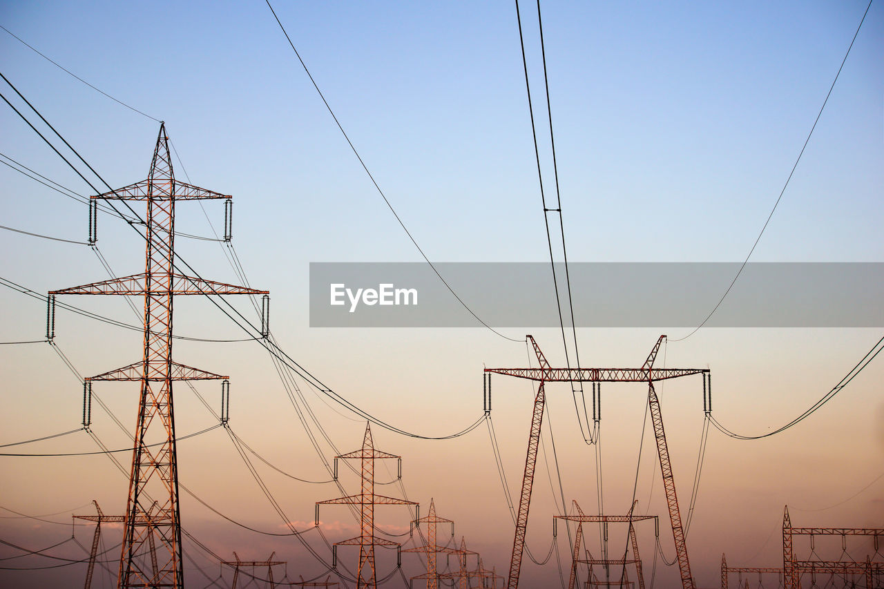 Electricity Pylons Against Sky At Sunset