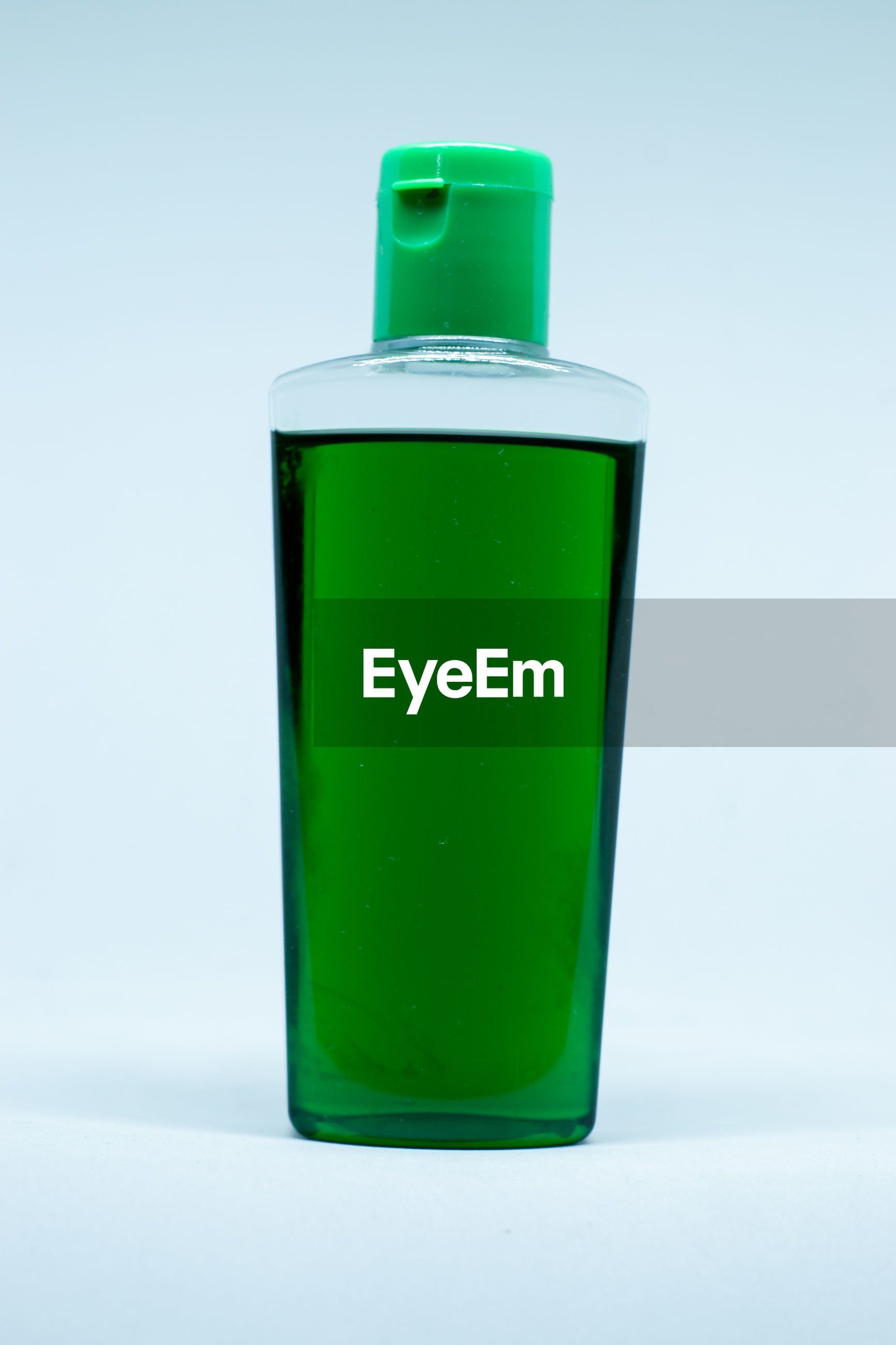 Close-up of green bottle against blue background