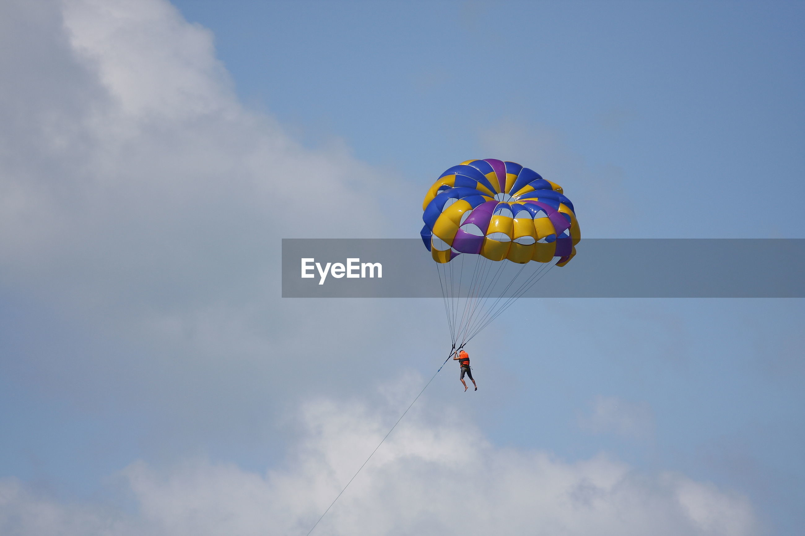 Low angle view of person skydiving with parachute against sky