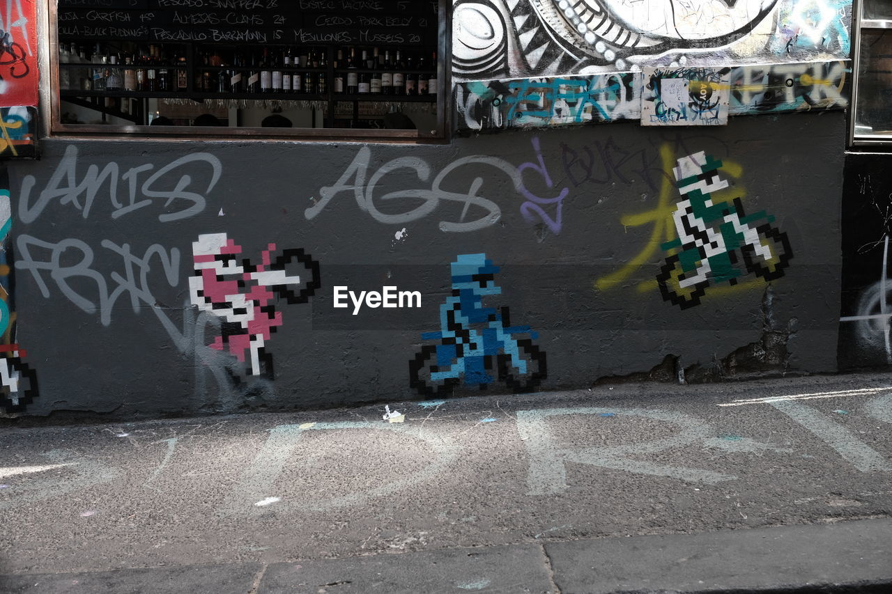 text, graffiti, architecture, communication, built structure, outdoors, building exterior, day, city, no people, neon