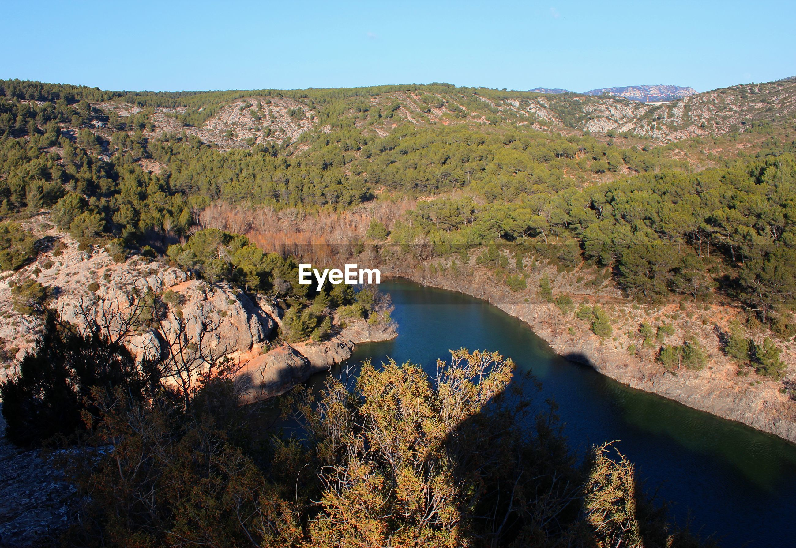 HIGH ANGLE VIEW OF RIVER AMIDST TREES AND MOUNTAINS AGAINST SKY