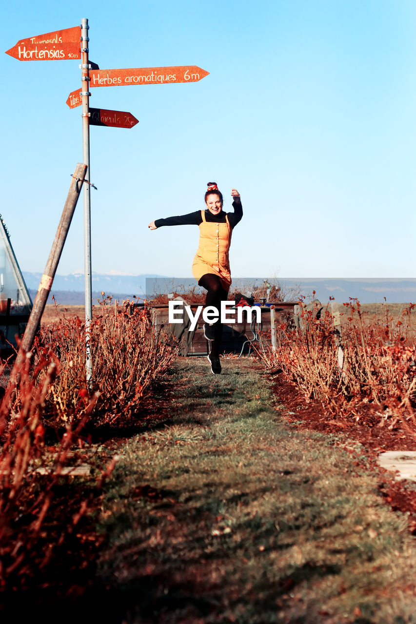 Full length of woman jumping amidst field