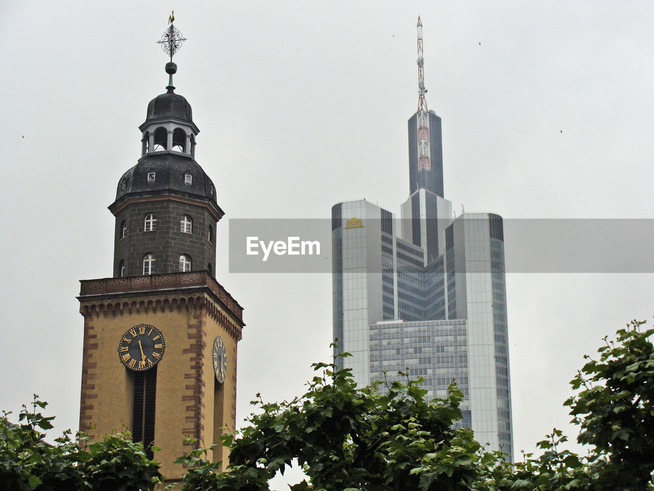 architecture, tower, building exterior, built structure, skyscraper, city, clock tower, tree, religion, sky, no people, clock, place of worship, outdoors, day, modern, bell tower, time
