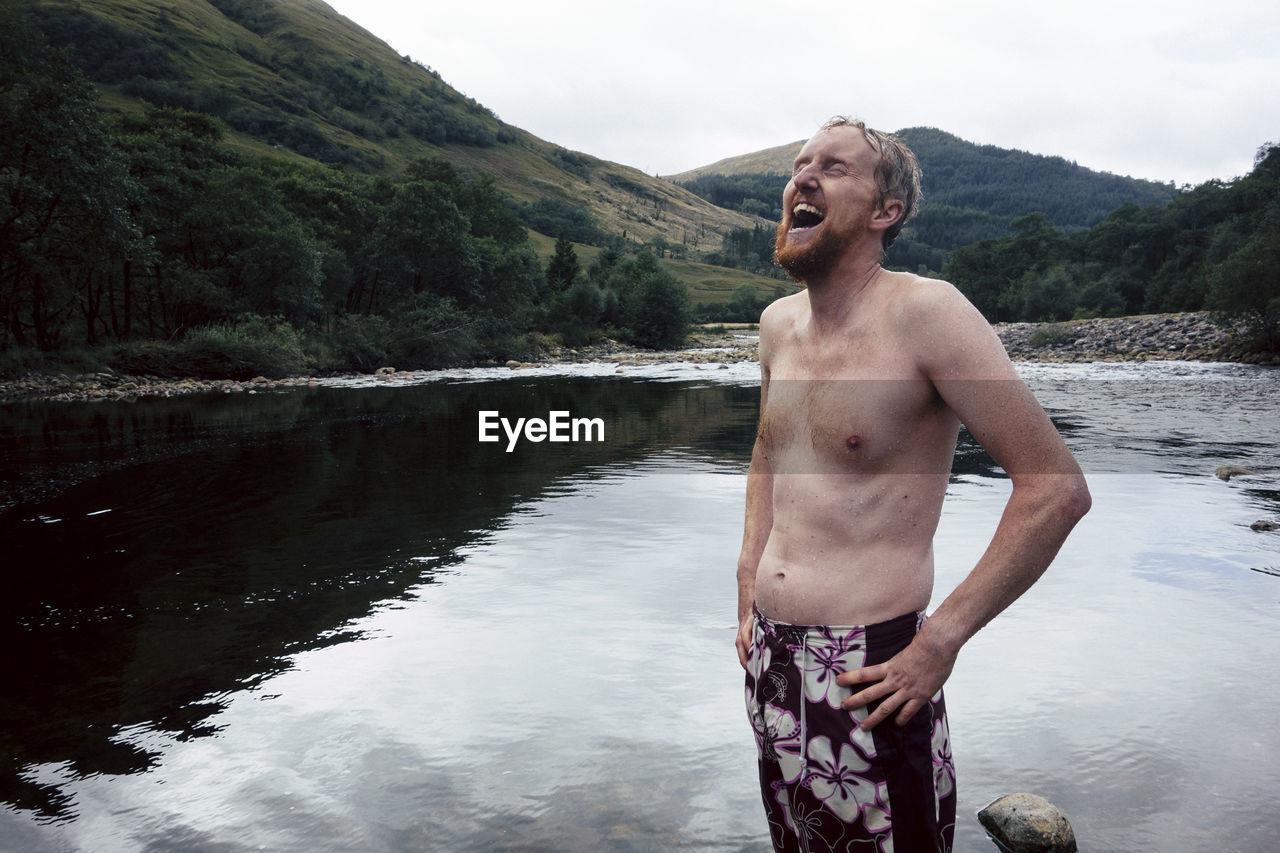 Shirtless laughing man standing at lake against sky