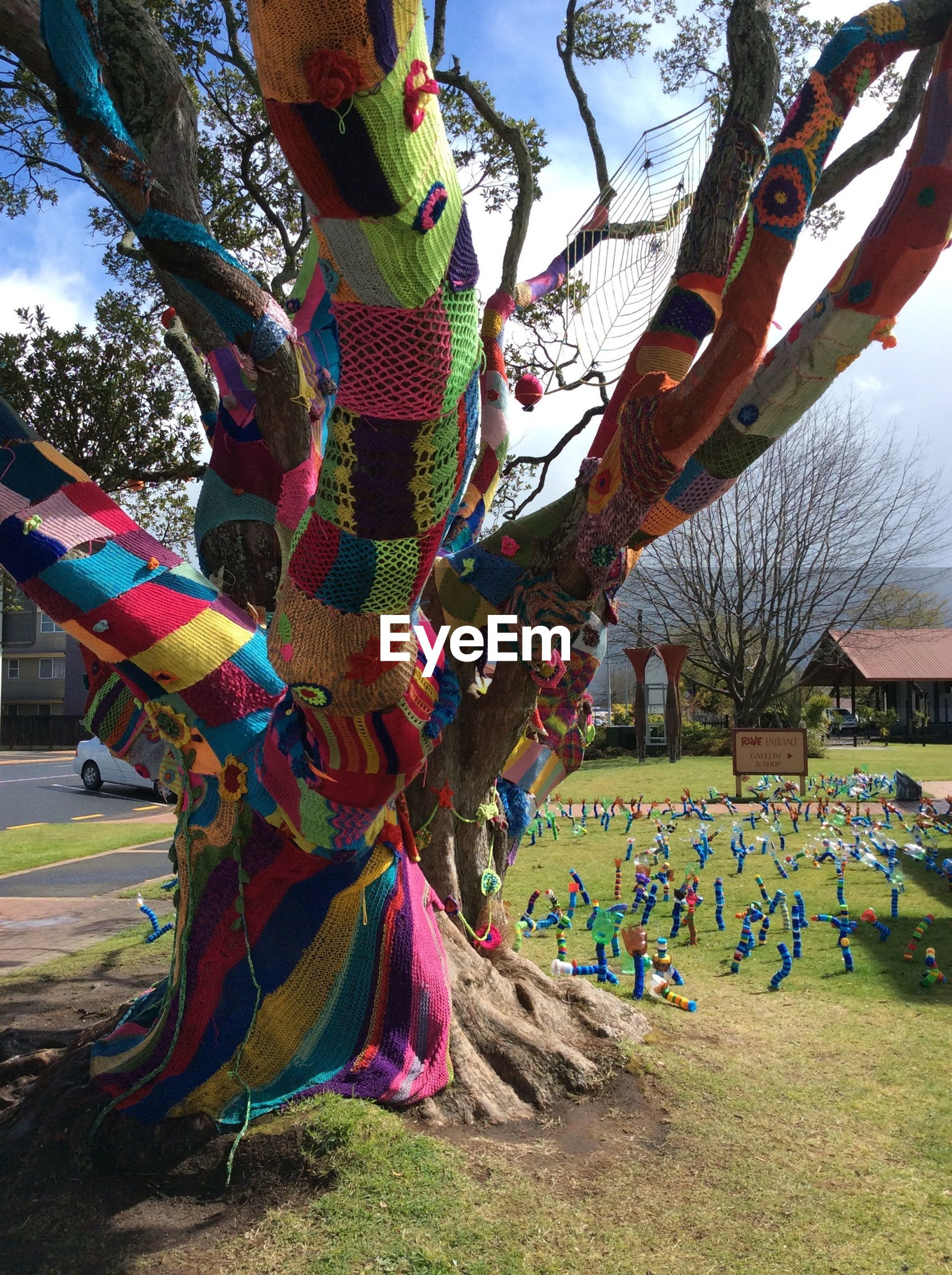 tree, sky, multi colored, day, hanging, sunlight, art and craft, outdoors, growth, park - man made space, field, tradition, incidental people, tree trunk, nature, cultures, creativity, grass, art