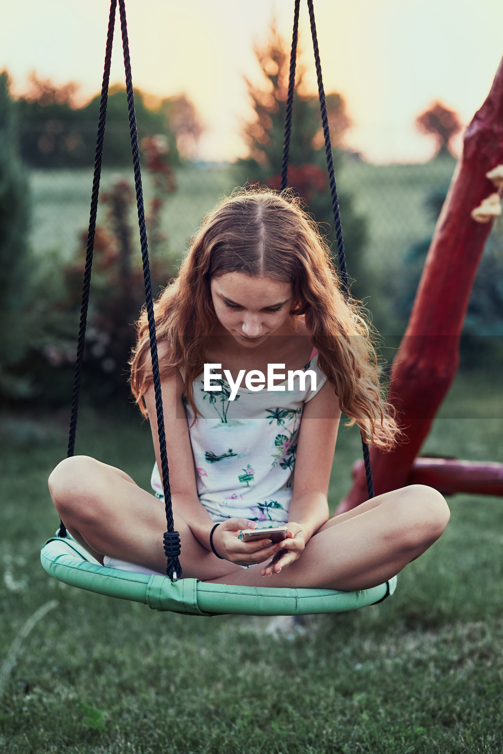 Girl using mobile phone while sitting on swing