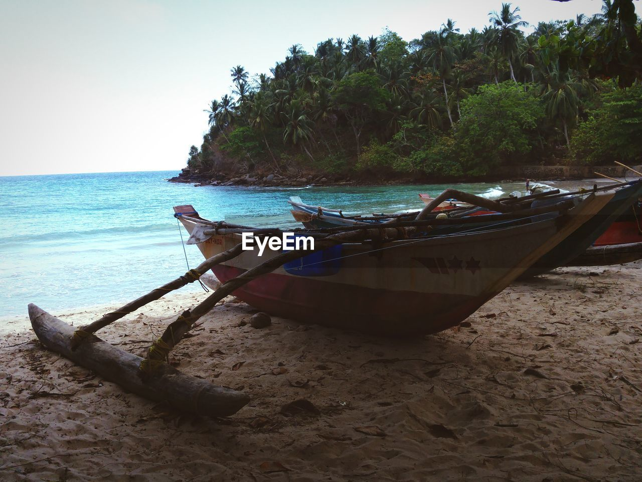 beach, sea, nature, water, shore, sand, nautical vessel, moored, longtail boat, scenics, beauty in nature, tranquil scene, transportation, mode of transport, horizon over water, tranquility, no people, outdoors, day, sky, clear sky, outrigger, tree