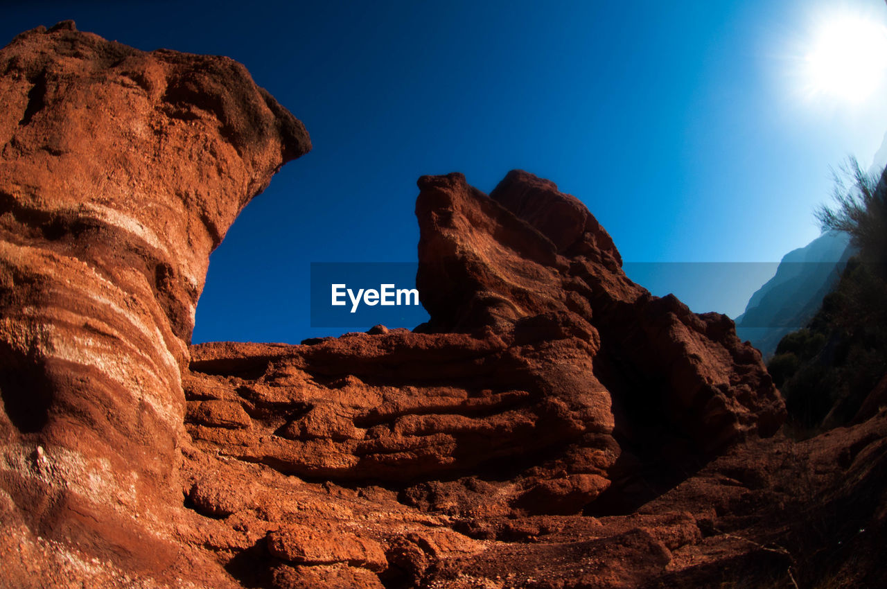 rock formation, rock, rock - object, solid, sky, geology, physical geography, nature, beauty in nature, sunlight, no people, low angle view, scenics - nature, non-urban scene, tranquil scene, blue, tranquility, clear sky, day, mountain, outdoors, eroded, natural arch, arid climate, climate, lens flare, formation, sandstone, mountain peak