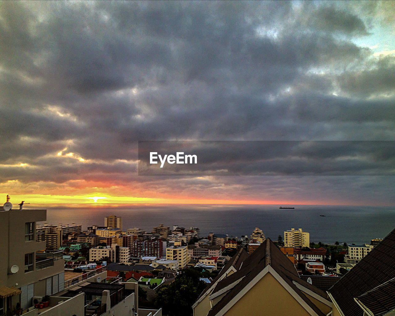 architecture, building exterior, cloud - sky, built structure, sky, city, cityscape, sunset, skyscraper, no people, city life, sea, outdoors, residential building, nature, storm cloud, horizon over water, beauty in nature, travel destinations, modern, scenics, water, urban skyline, day
