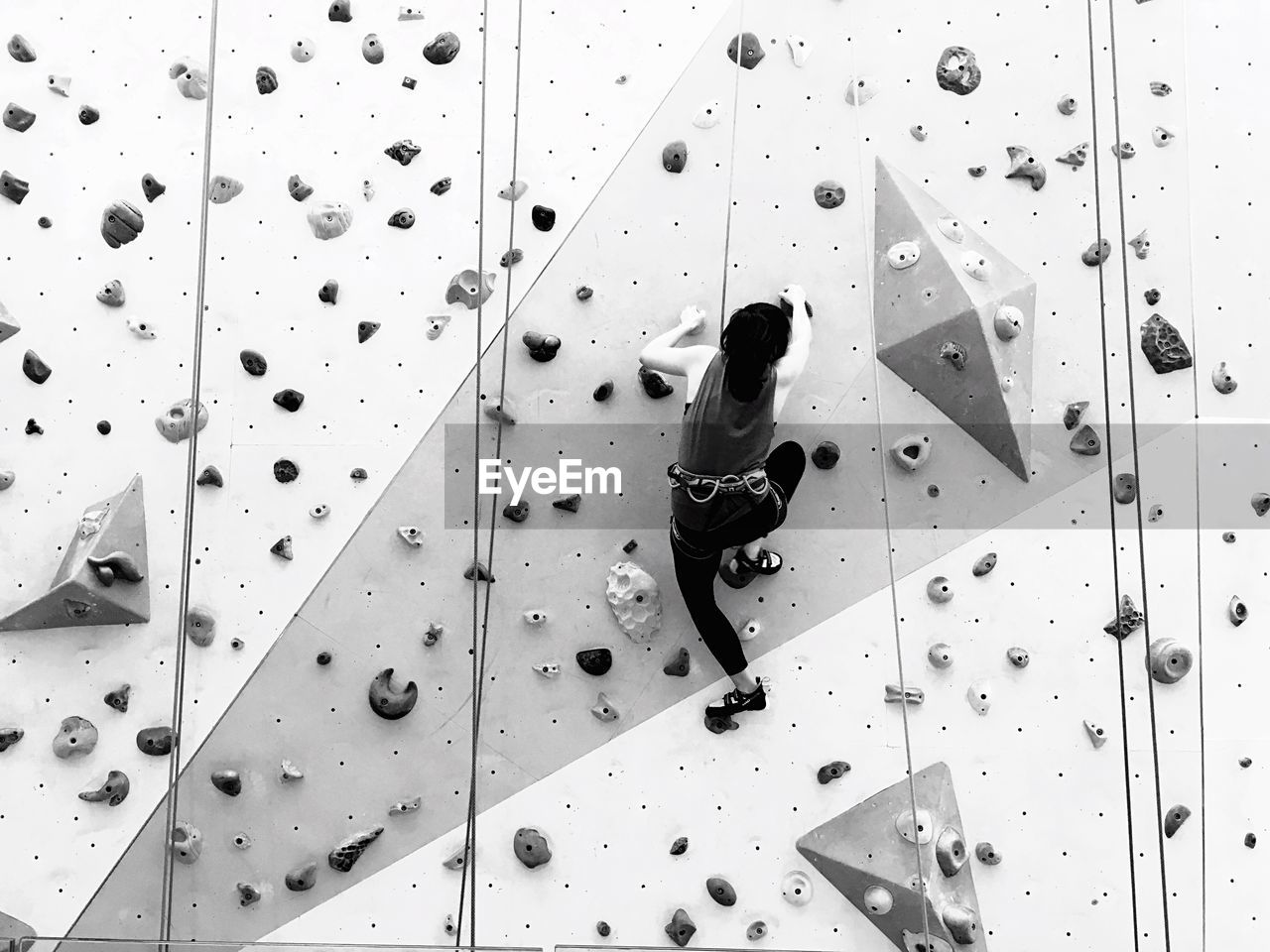 Low angle view of woman practicing rock climbing at gym