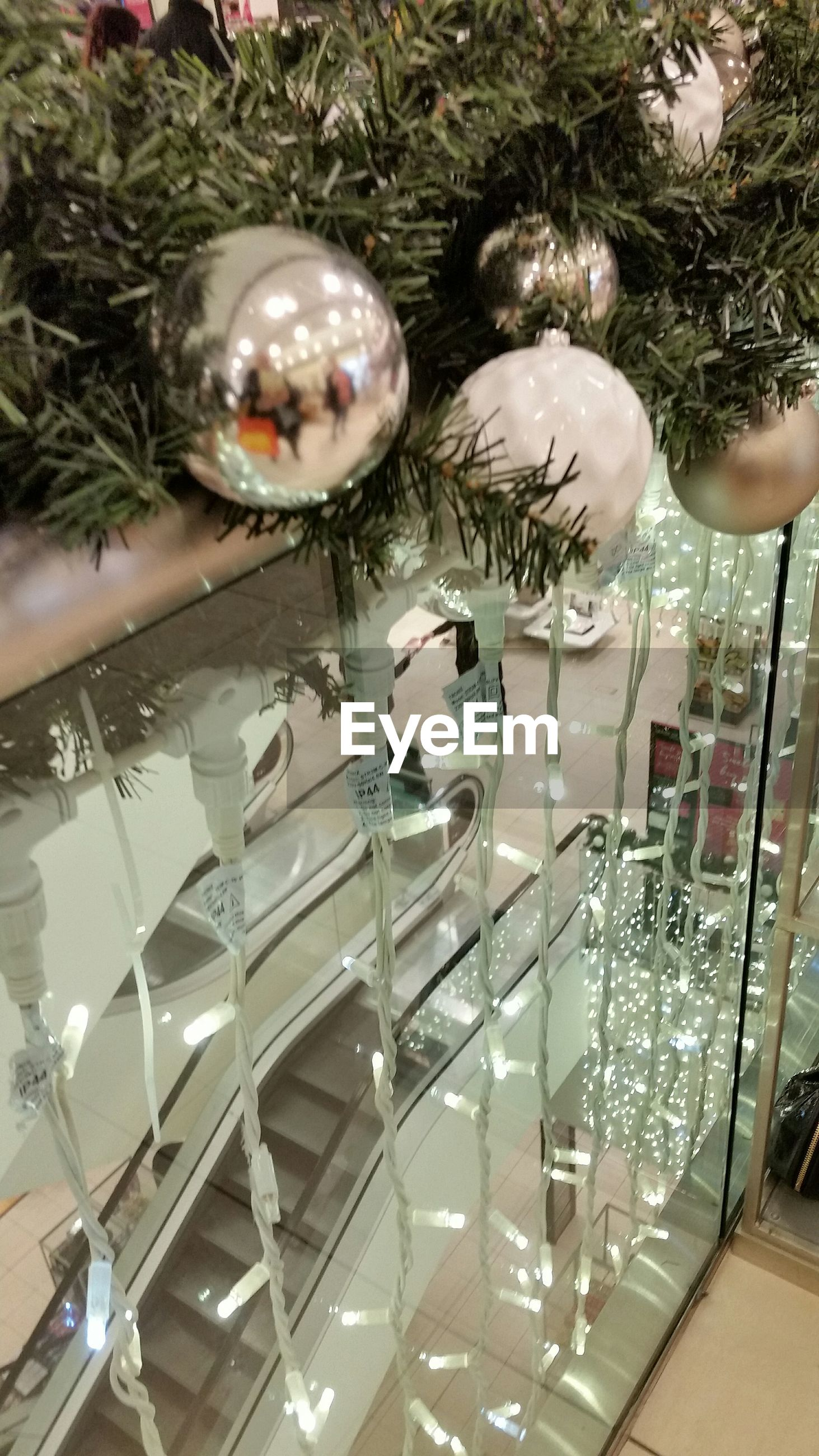 Christmas tree by lighting on glass railing in shopping mall