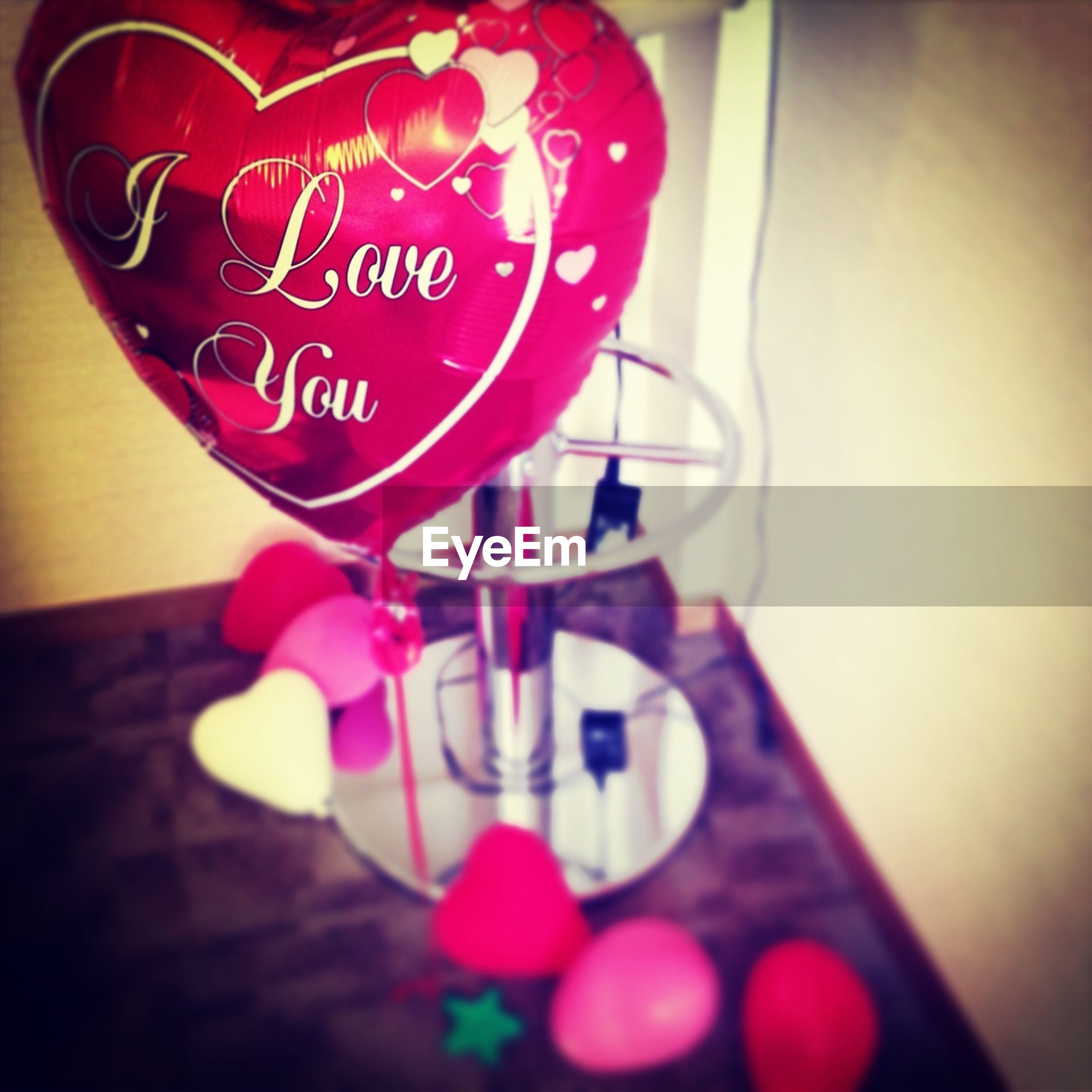 indoors, text, close-up, red, still life, communication, western script, table, focus on foreground, selective focus, decoration, hanging, pink color, heart shape, no people, celebration, love, glass - material, illuminated, lighting equipment