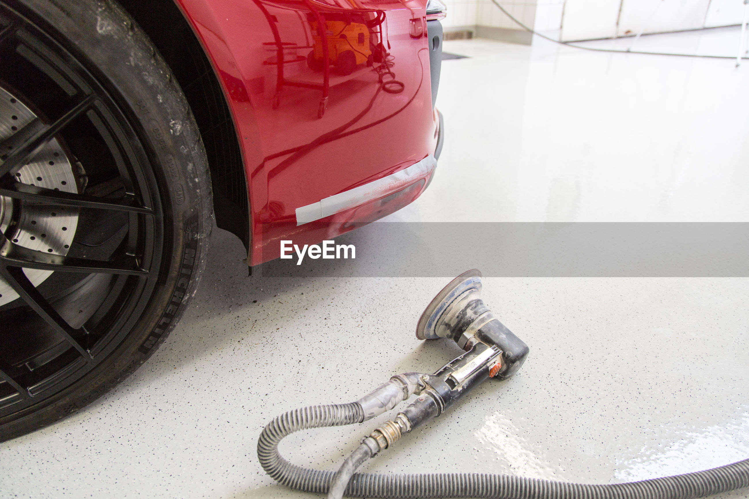 High angle view of electric sander by car at repair shop