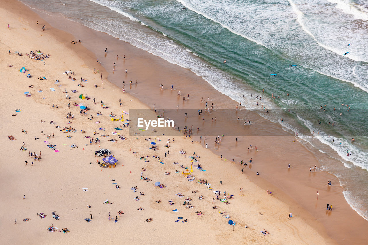 land, sand, beach, crowd, high angle view, water, sea, large group of people, group of people, trip, vacations, holiday, real people, nature, motion, day, wave, beauty in nature, sport, outdoors