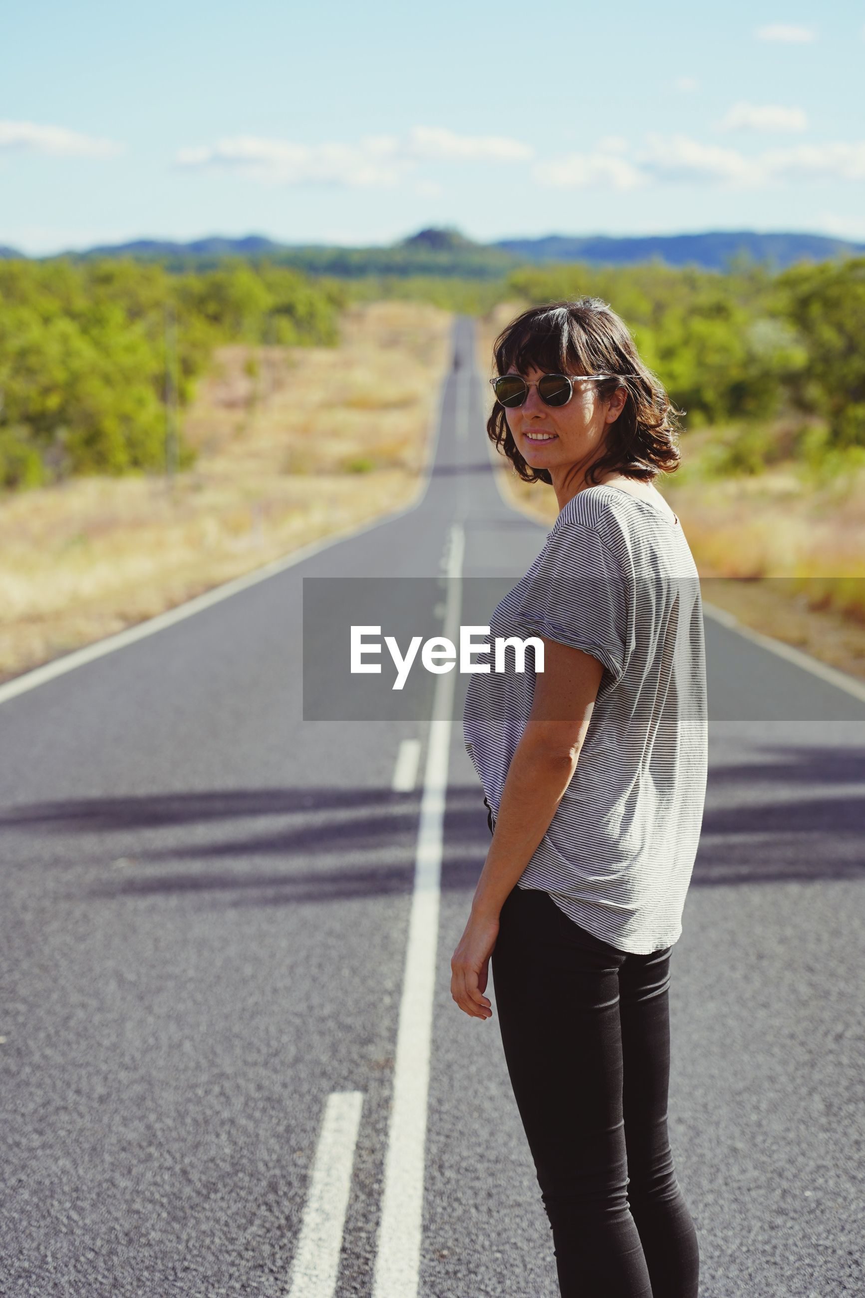 Portrait of woman wearing sunglasses standing on road