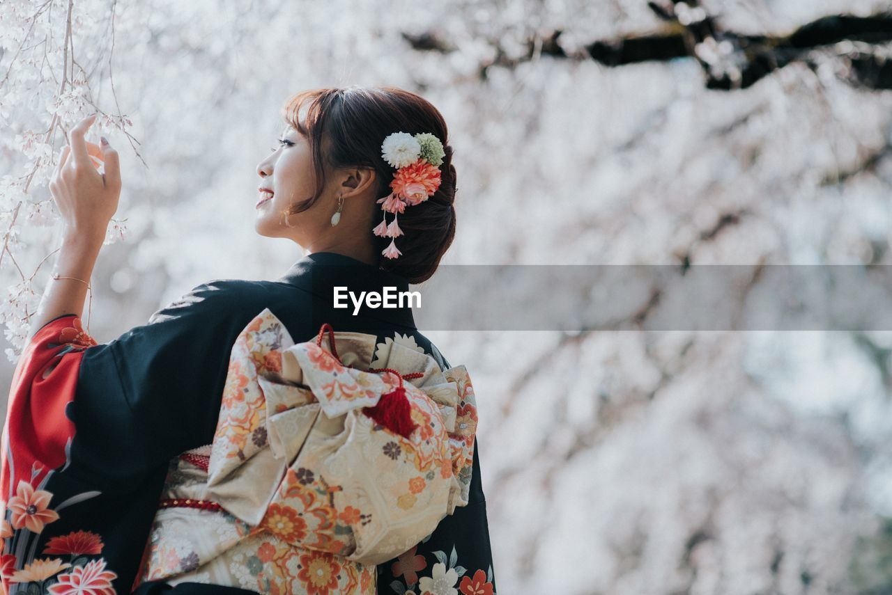 Low Angle View Of Woman In Kimono Standing By Cherry Blossoms