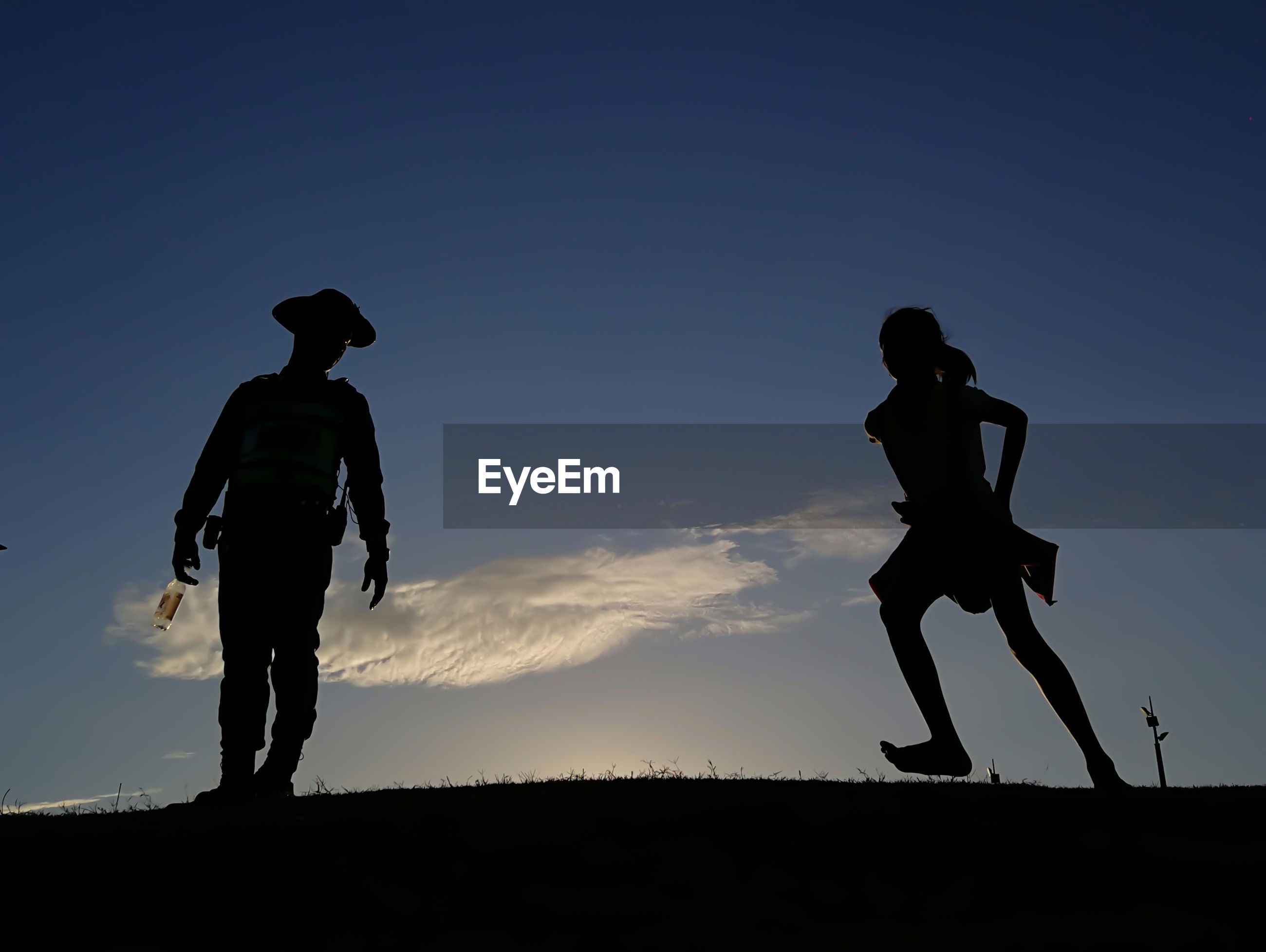 LOW ANGLE VIEW OF SILHOUETTE MEN STANDING ON FIELD AGAINST SKY DURING SUNSET