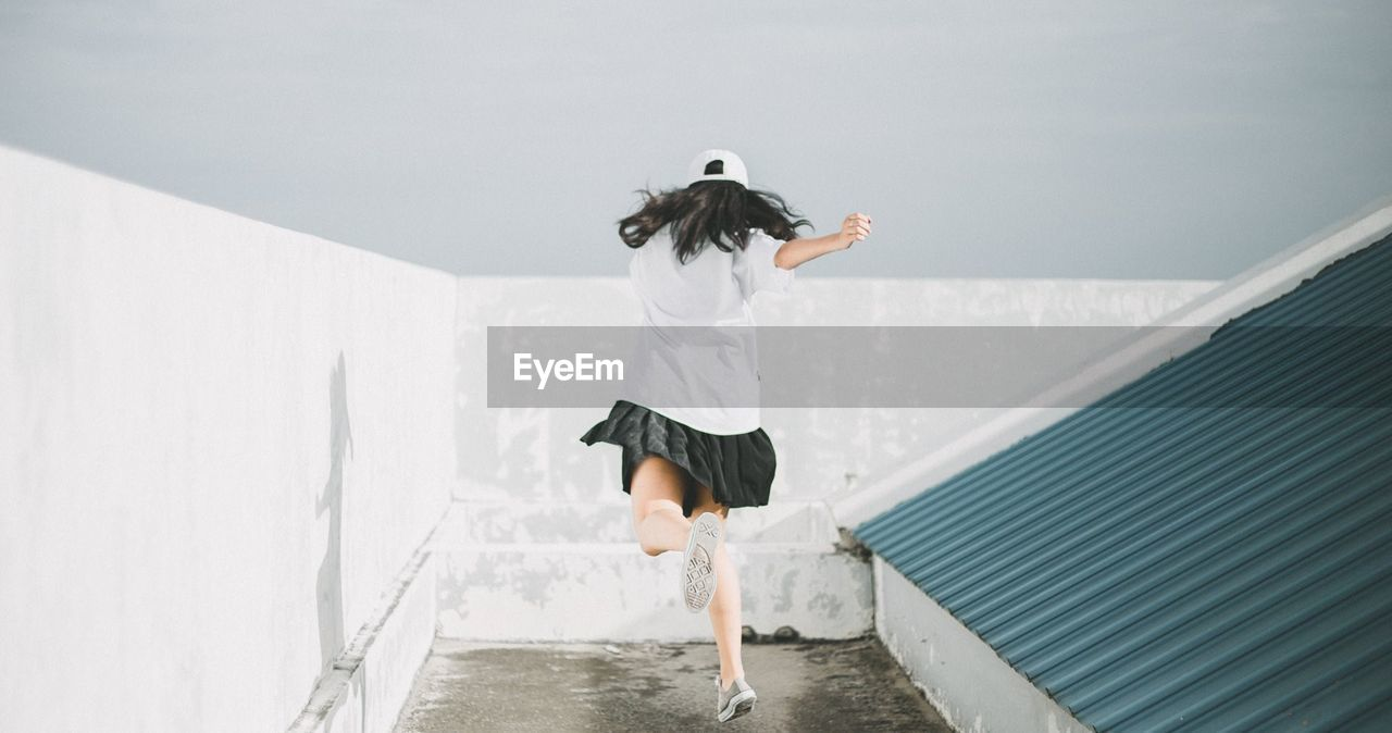 Rear View Of Woman Jumping By Wall Against Sky