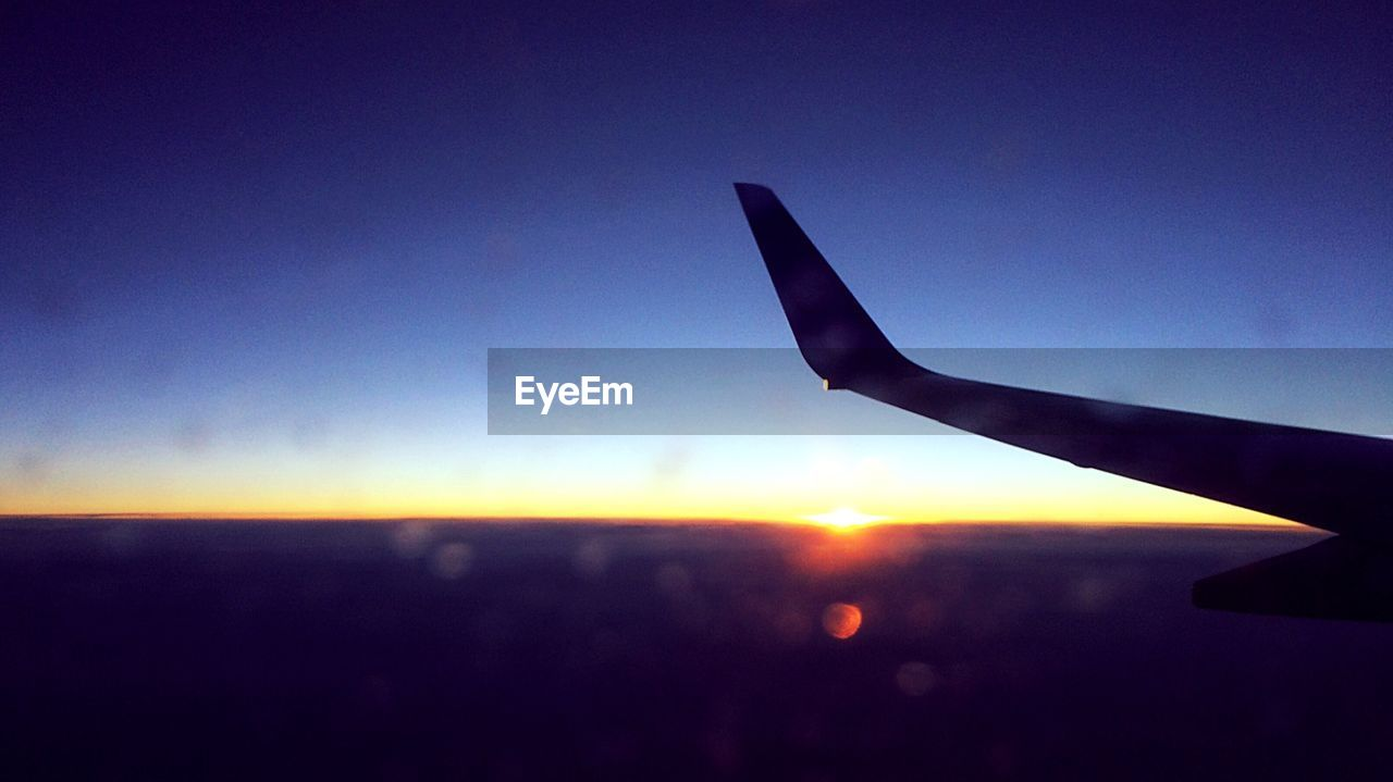 airplane, sky, sunset, air vehicle, silhouette, airplane wing, journey, aircraft wing, transportation, flying, nature, blue, beauty in nature, scenics, outdoors, mid-air, tranquility, no people, close-up, day