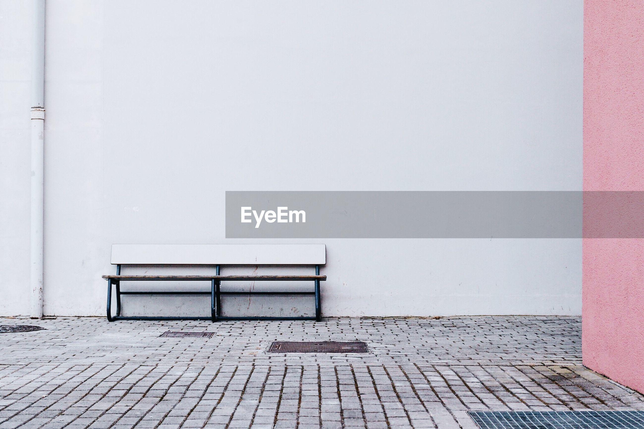 Empty bench on sidewalk against white wall