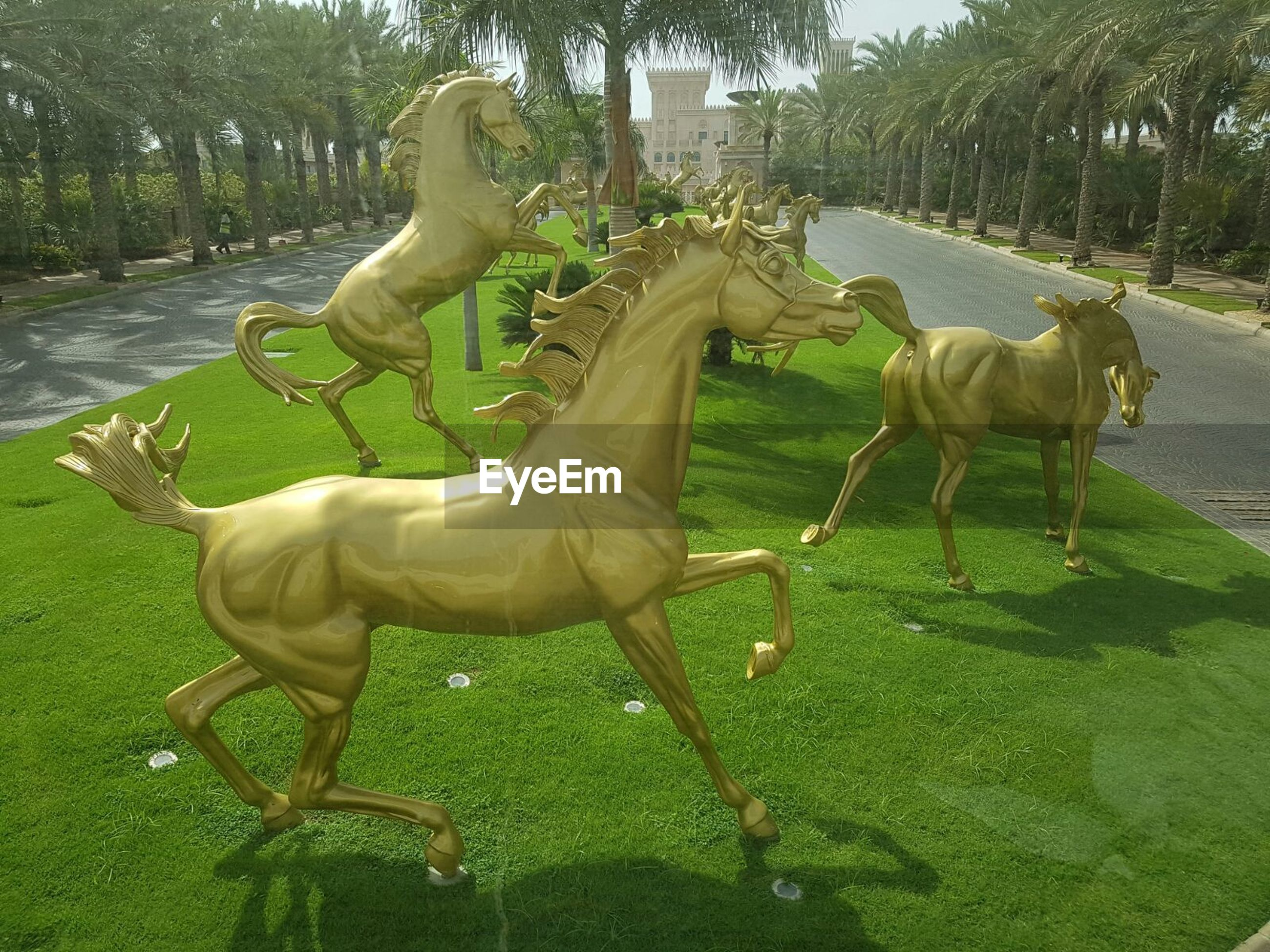 animal themes, tree, grass, park - man made space, mammal, one animal, sunlight, horse, green color, domestic animals, full length, sculpture, day, outdoors, field, two animals, nature, no people, shadow, animal representation